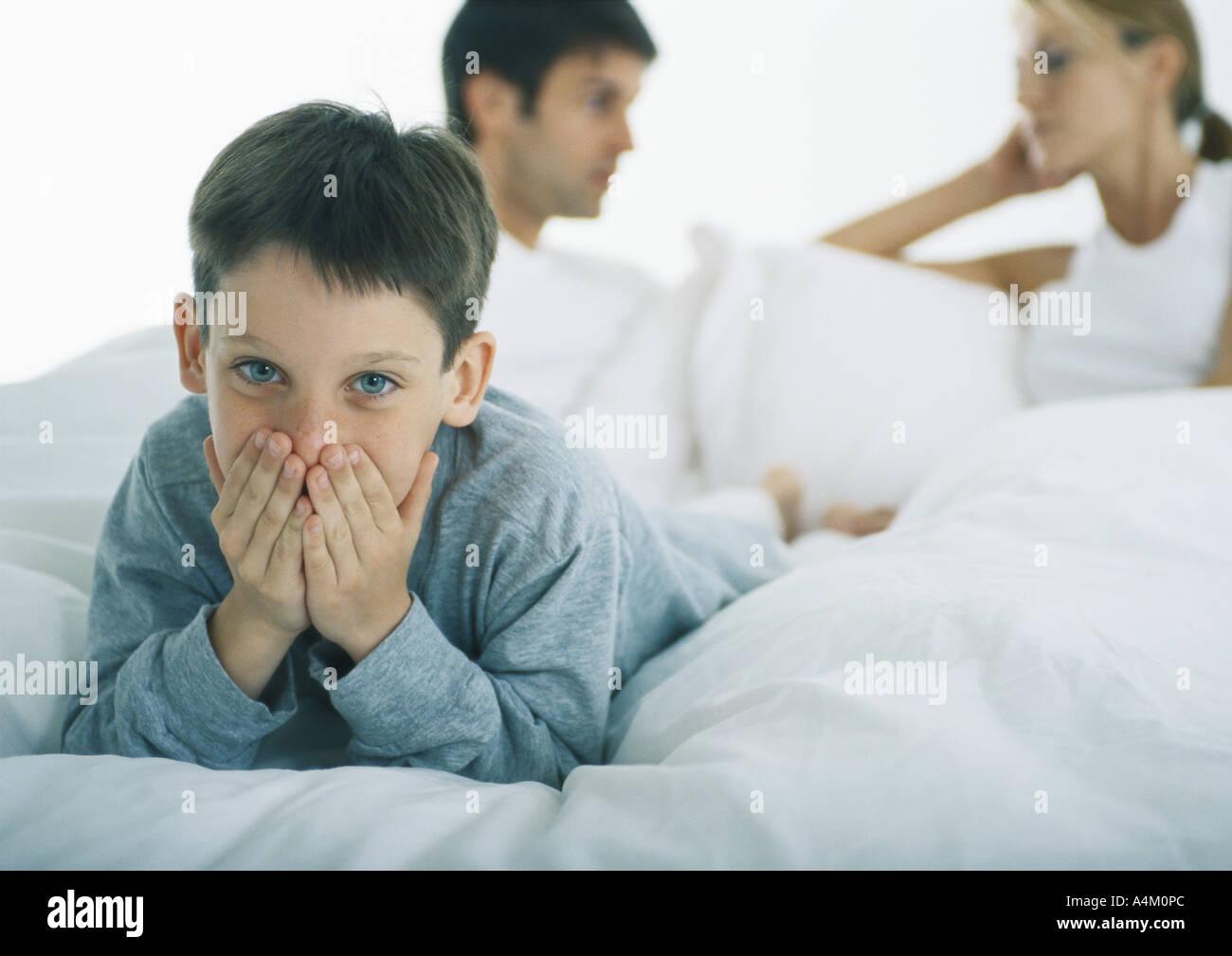 Boy lying on stomach in bed couvrant la bouche avec les mains, les parents de discuter en arrière-plan Banque D'Images