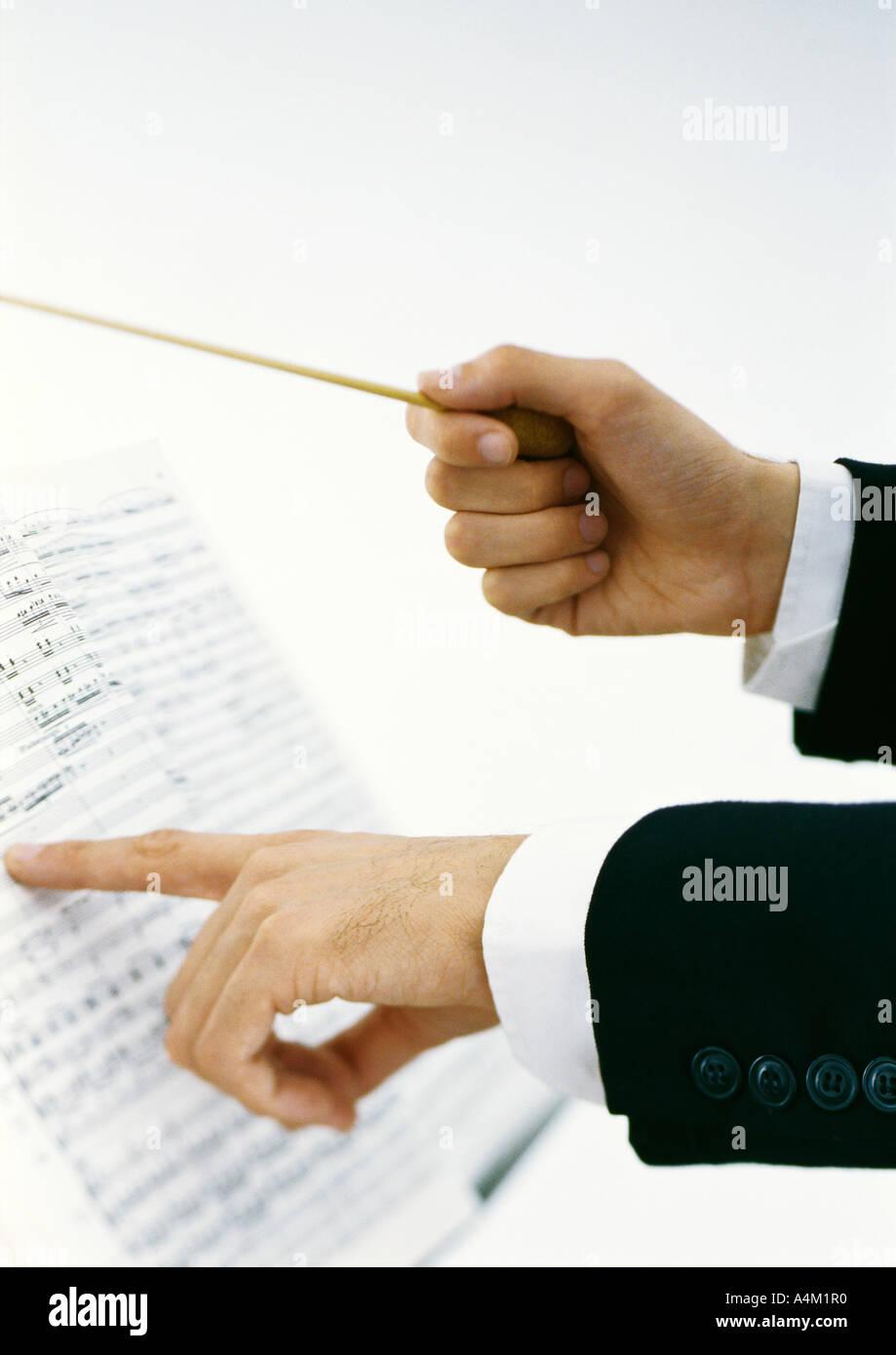 Conductor's hands holding baton et en pointant sur Sheet Music Photo Stock