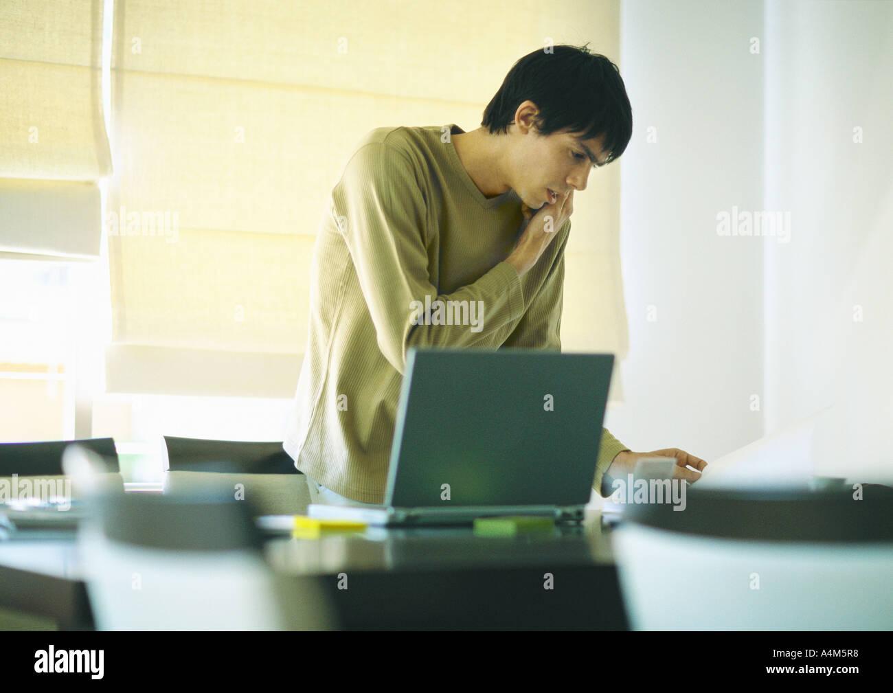 Jeune homme à l'aide de téléphone et ordinateur portable Photo Stock
