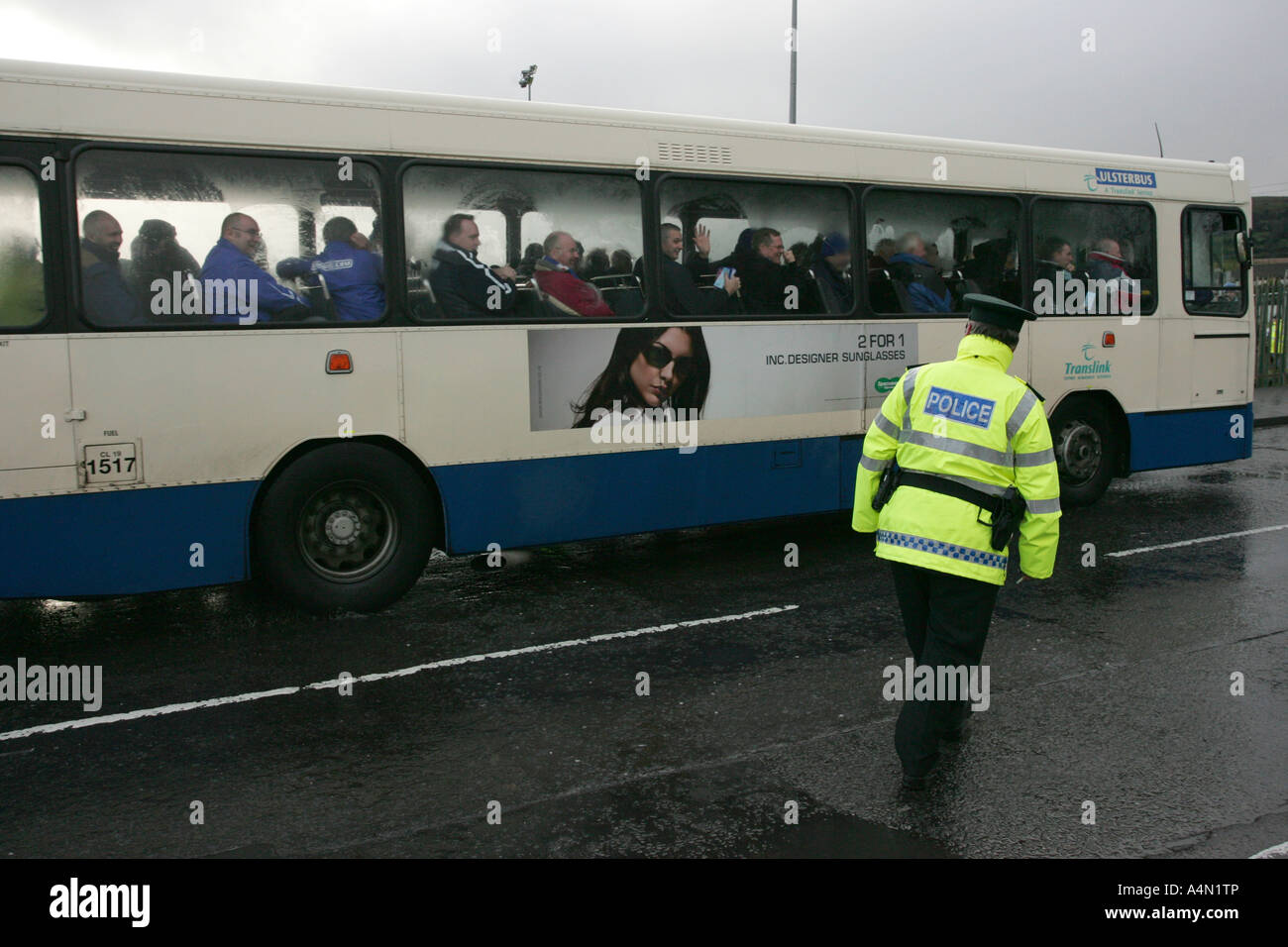 Policier PSNI en hi vis jacket escorts ulster bus plein de linfield partisans à travers la zone républicaine Photo Stock
