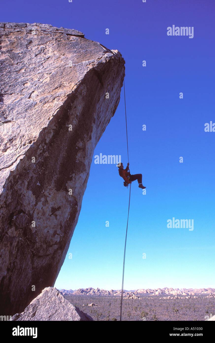 Climing rock man rappeling off rock avec en arrière-plan du paysage désertique Joshua Tree California USA Photo Stock