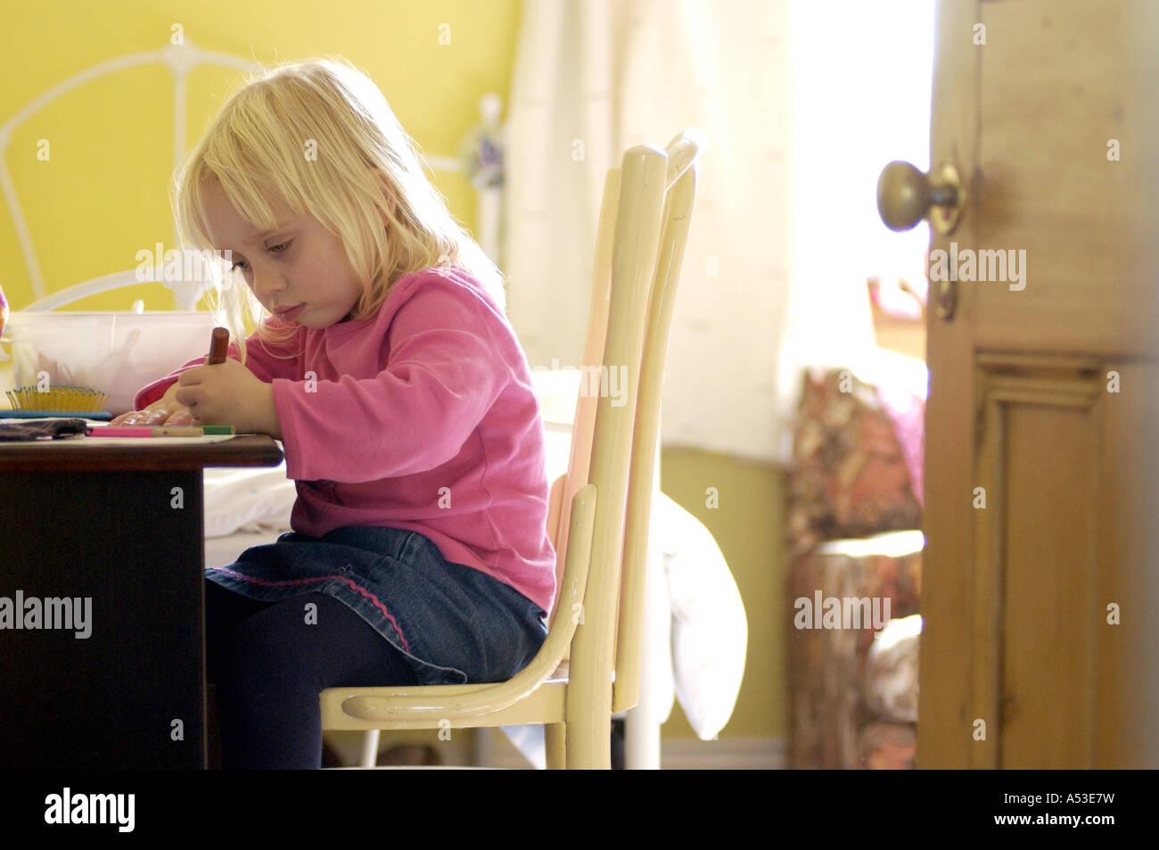 La jeune enfant à faire leurs devoirs dans la chambre London UK avec l'impression de l'atmosphère Photo Stock