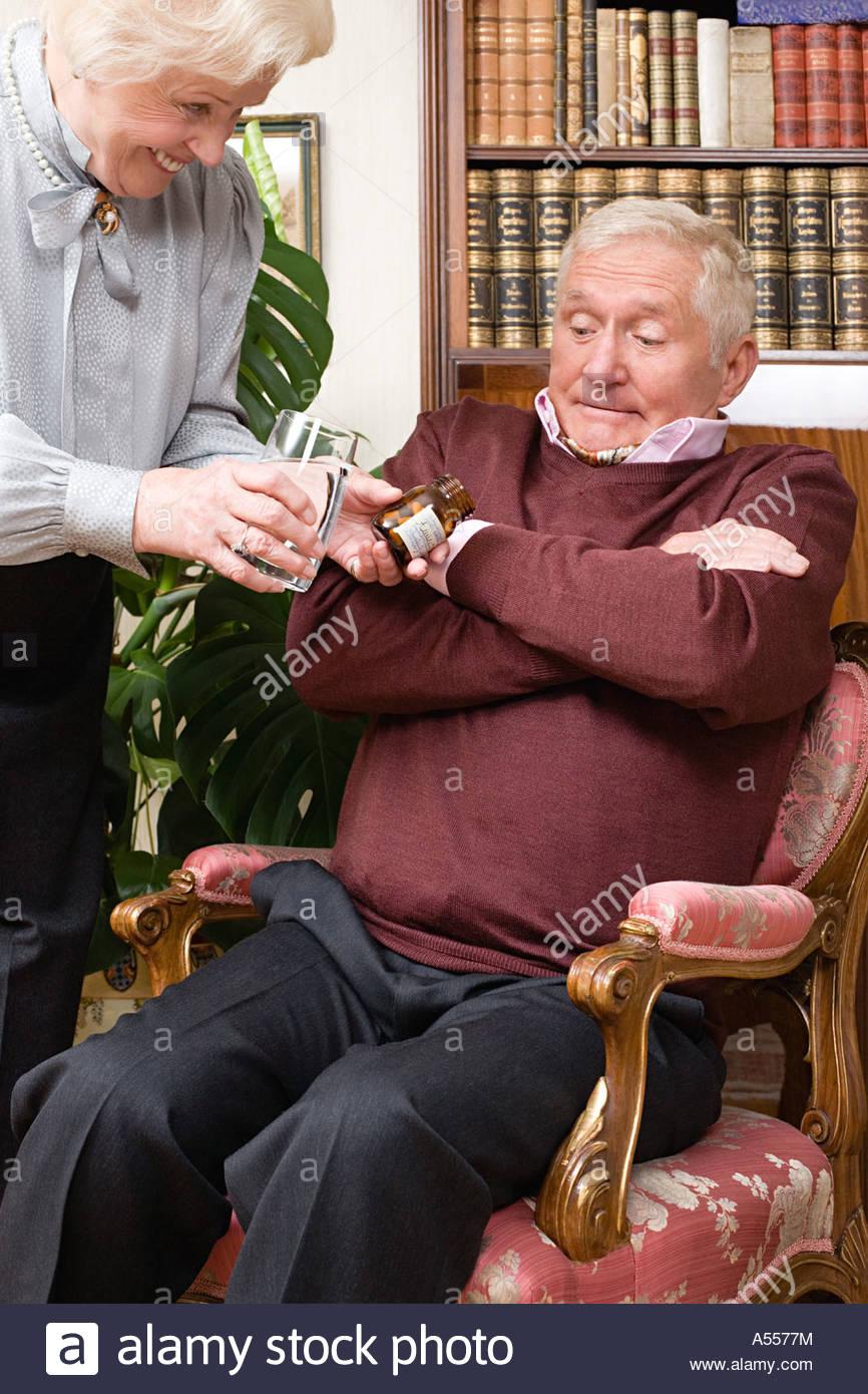 Femme essayant de donner les comprimés de mari Photo Stock