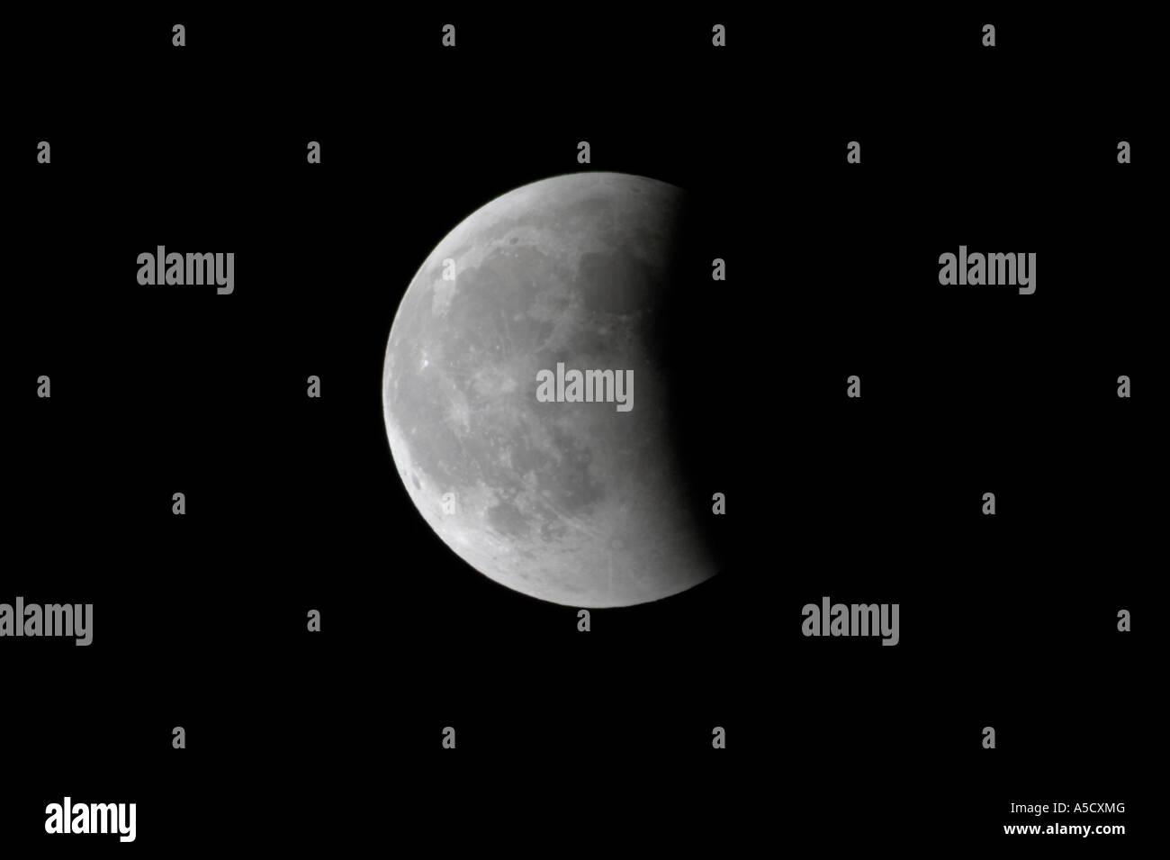 Près de la lune est sorti de l'ombre de la terre à la fin d'une éclipse lunaire totale comme Photo Stock