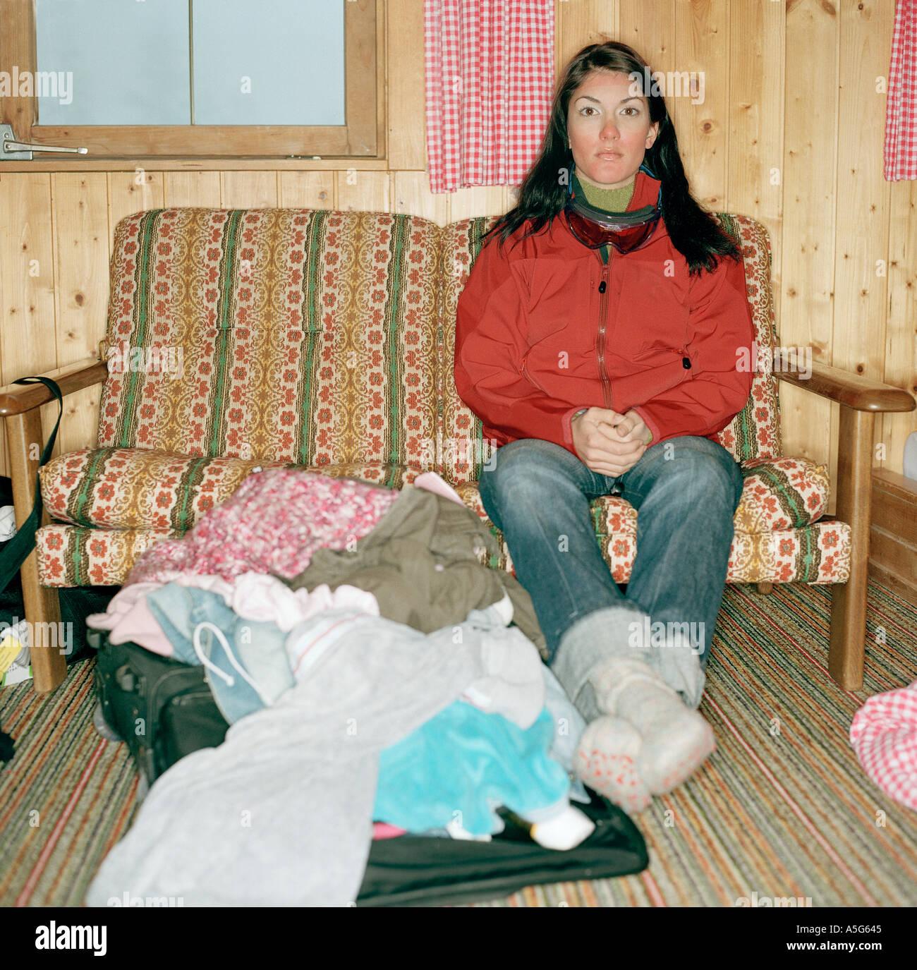Femme assise sur un sofa dans un chalet dans les alpes Banque D'Images