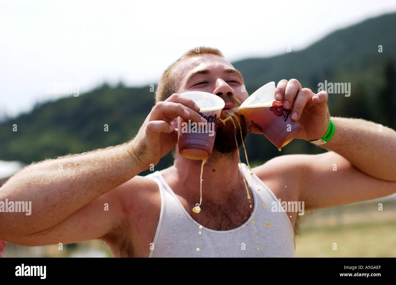 Guy boire deux bières dans un concert en plein air Photo Stock