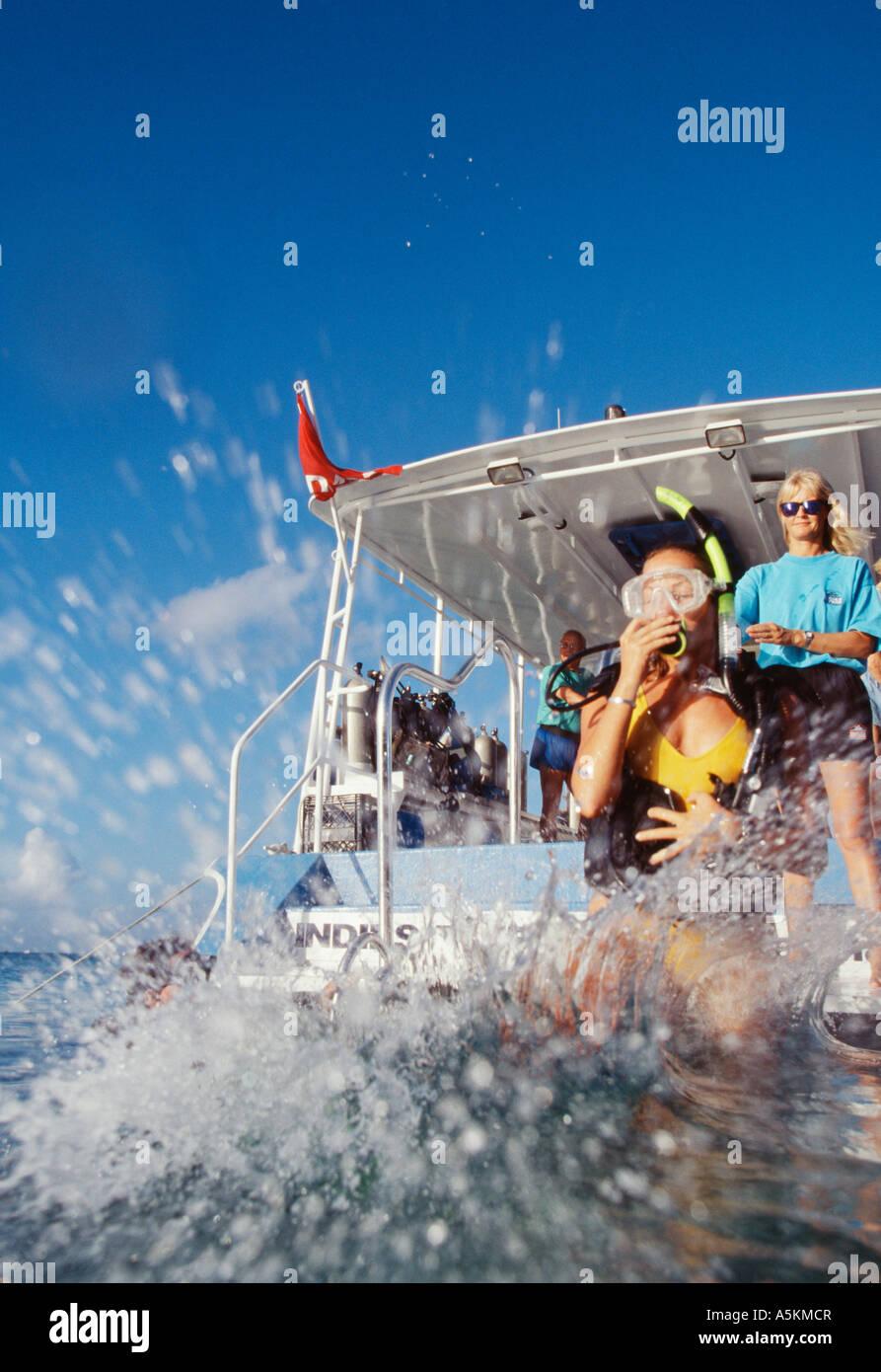 Grand Cayman Diver prend pas de géant au large bord de bateau de plongée Photo Stock
