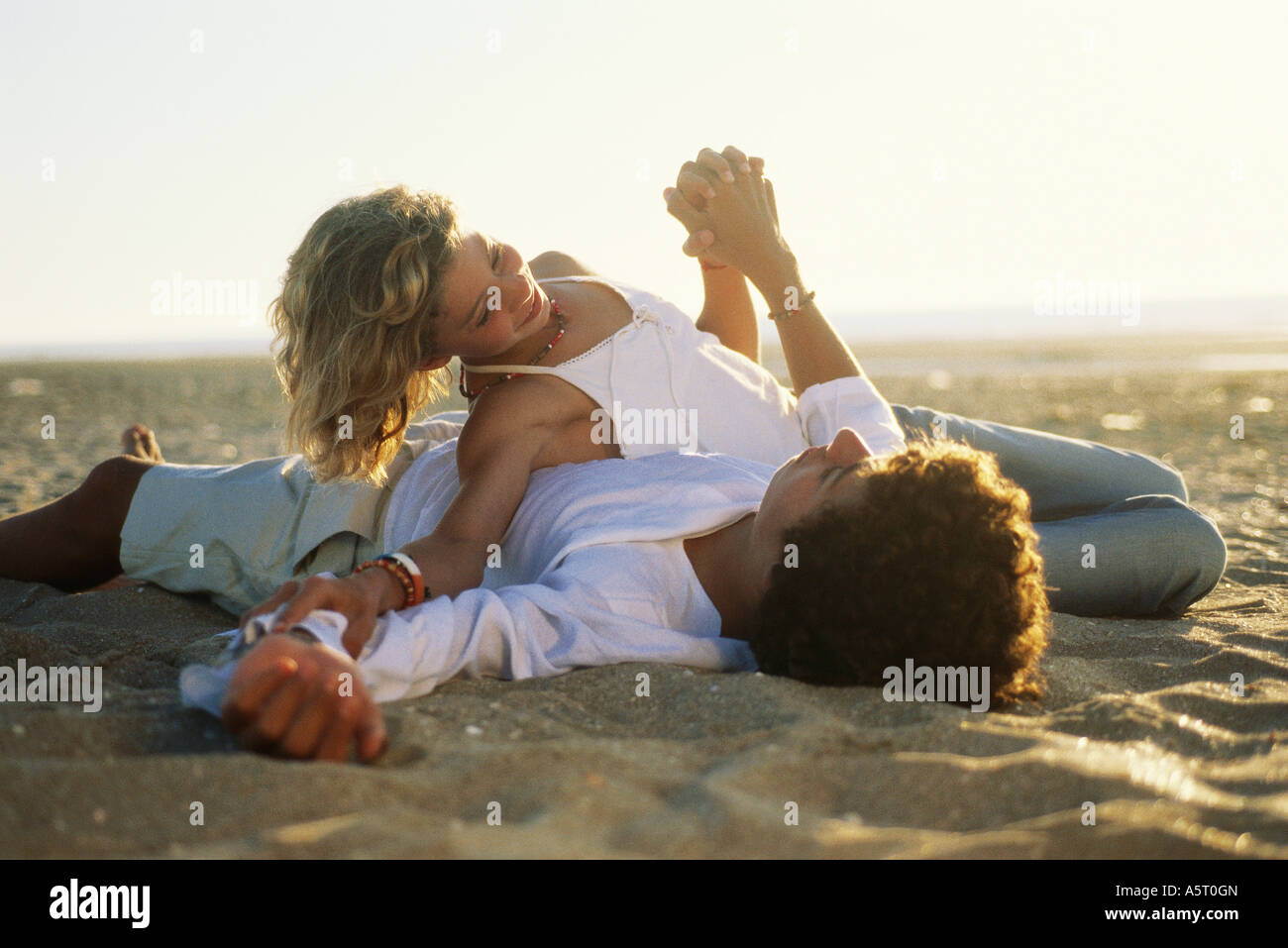 Teen couple lying on beach Banque D'Images
