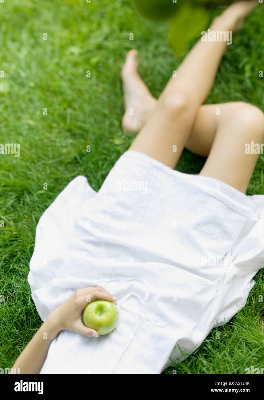 Woman lying in grass, holding apple, low section Photo Stock