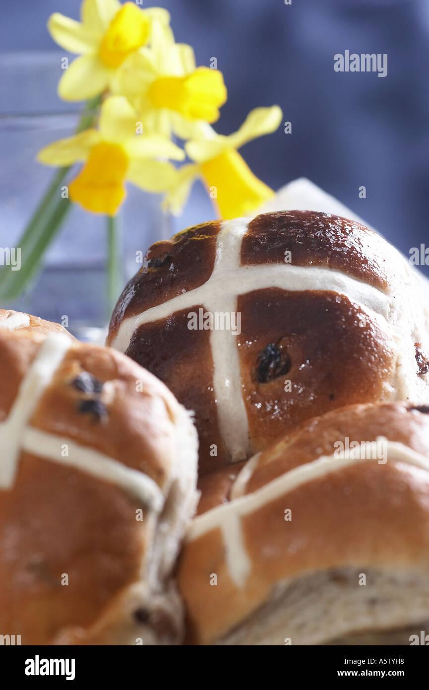 Hots les brioches sur la table du petit déjeuner avec fleurs de Pâques Photo Stock