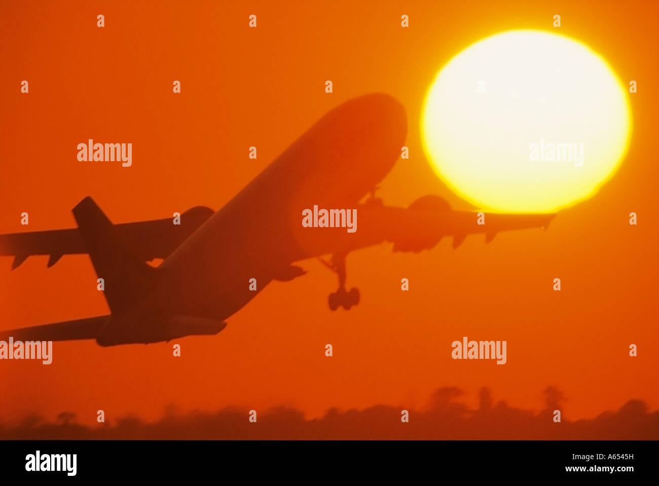 Avion au décollage dans le soleil couchant Photo Stock