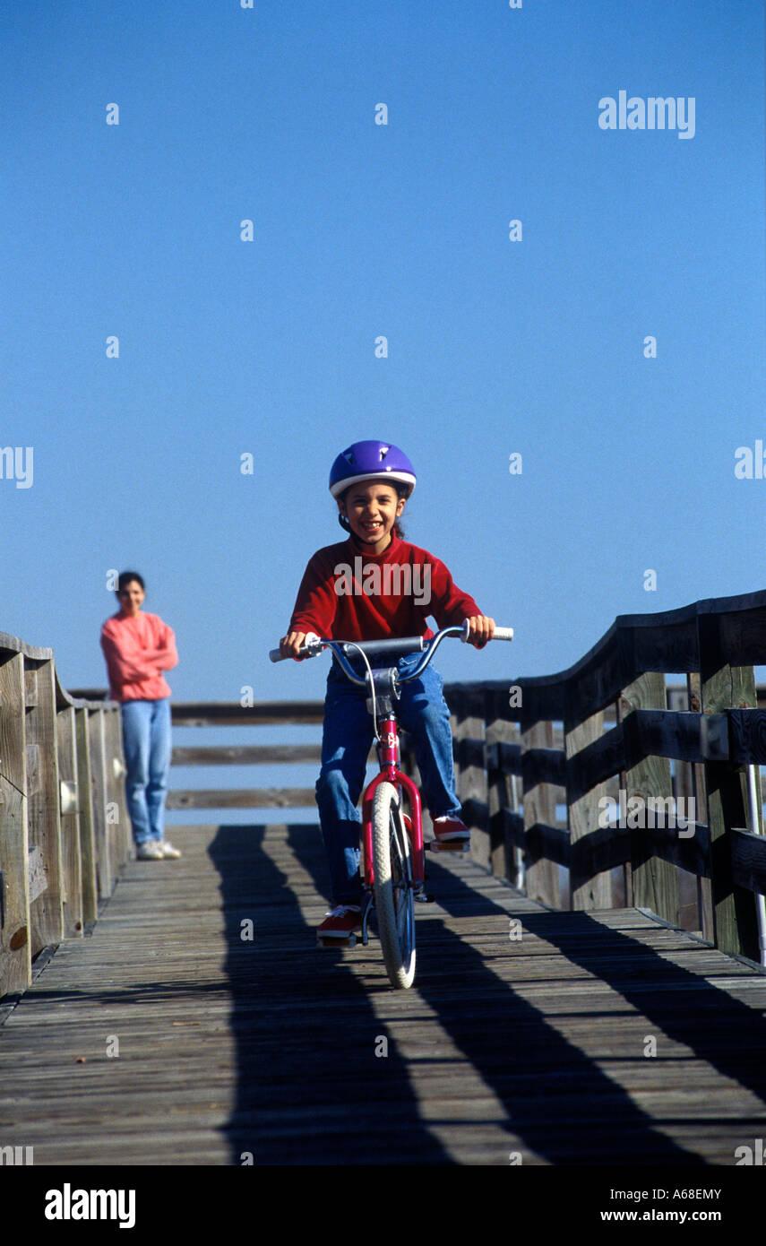 Fille d'apprendre à monter un vélo comme sa mère montres. Photo Stock