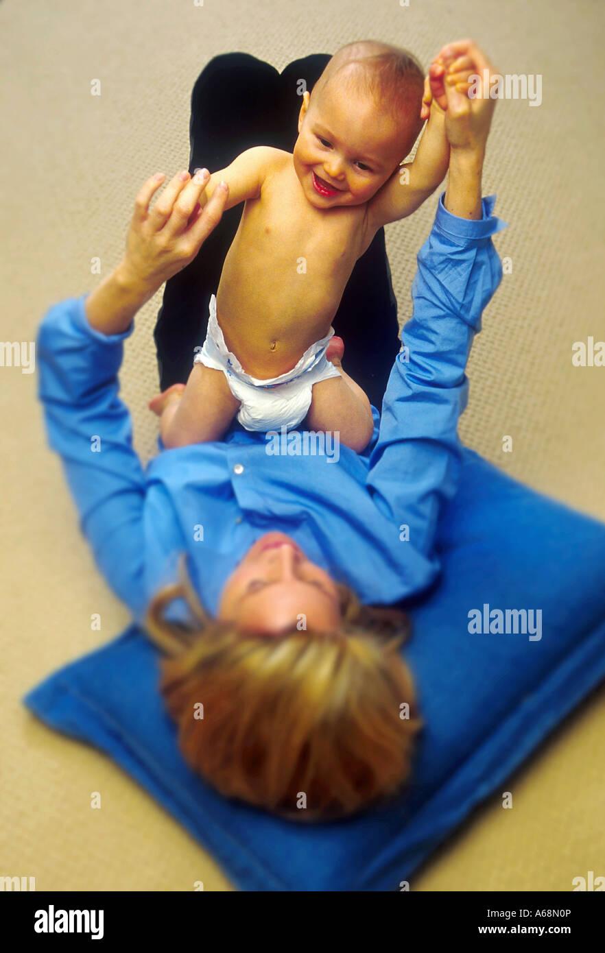 Un bébé souriant et mère à jouer Photo Stock