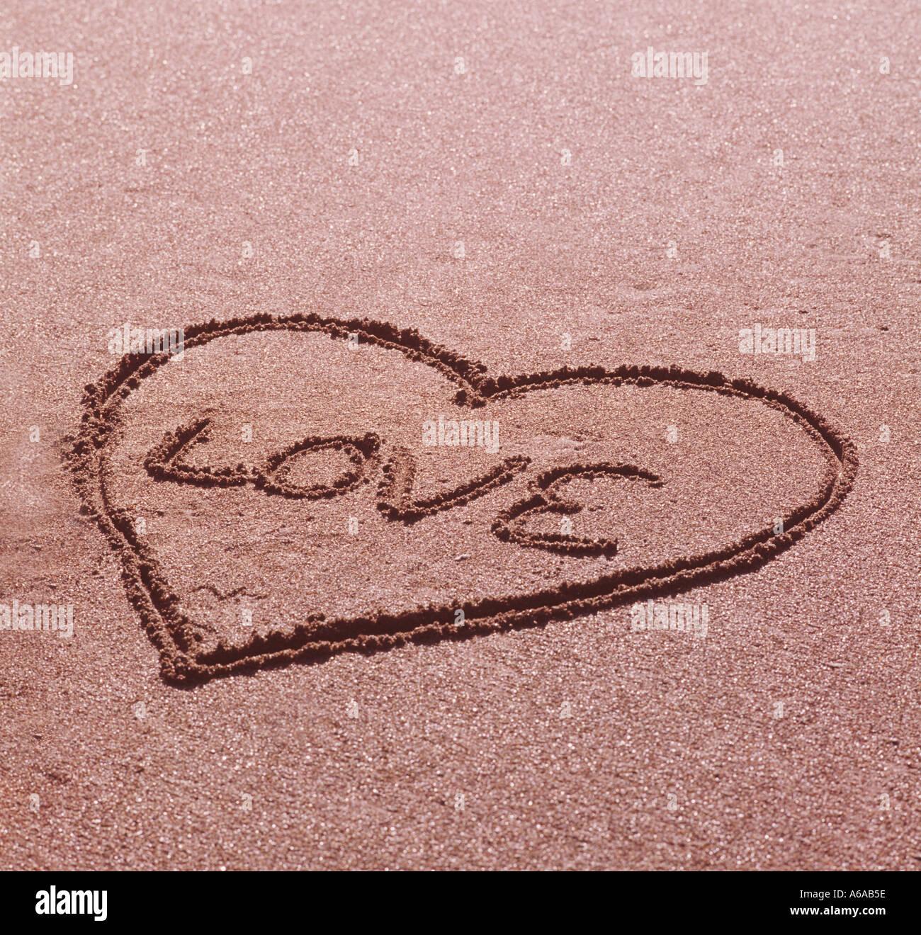 Valentine love symbole dessiné dans le sable à la plage Photo Stock