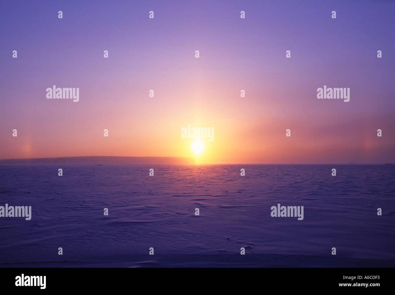 Coucher du soleil avec les sundogs et pilier de lumière causé par des cristaux de glace en suspension du Groenland Banque D'Images