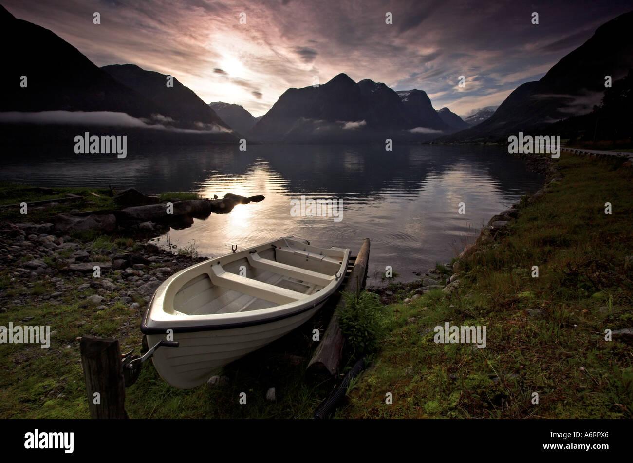 Un petit bateau attachés sur les rives d'un fjord norvégien. Traînée de bas nuage flottant sur les eaux calmes Photo Stock