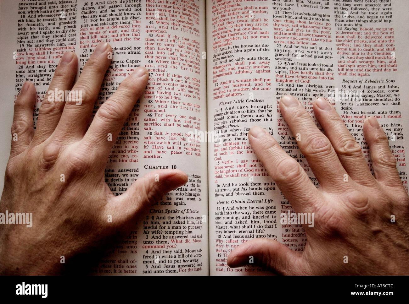 Mains sur Bible ouverte Banque D'Images