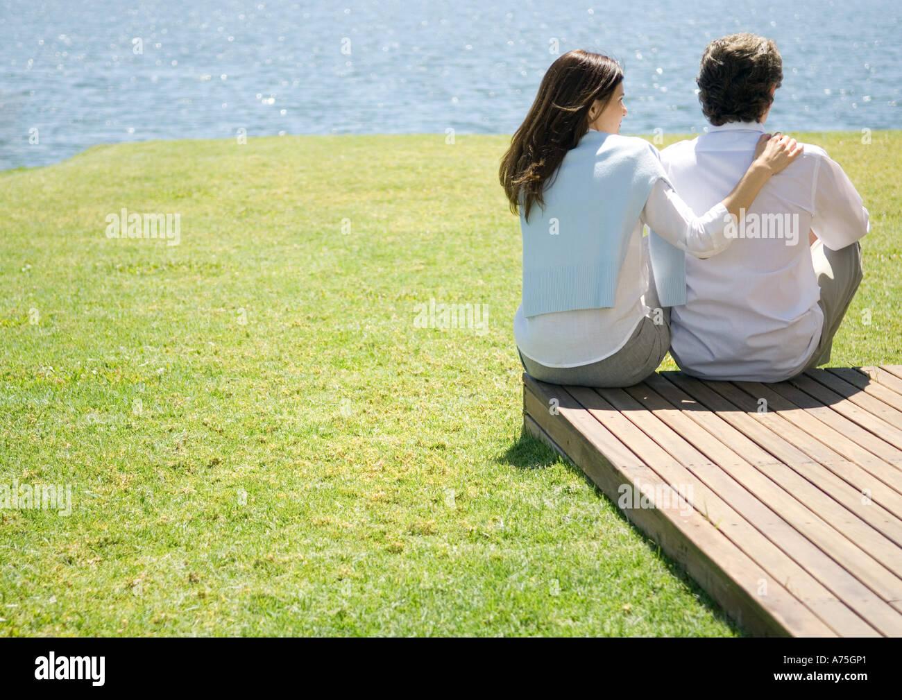 Couple à la fin de l'allée en bois, près de l'eau Banque D'Images