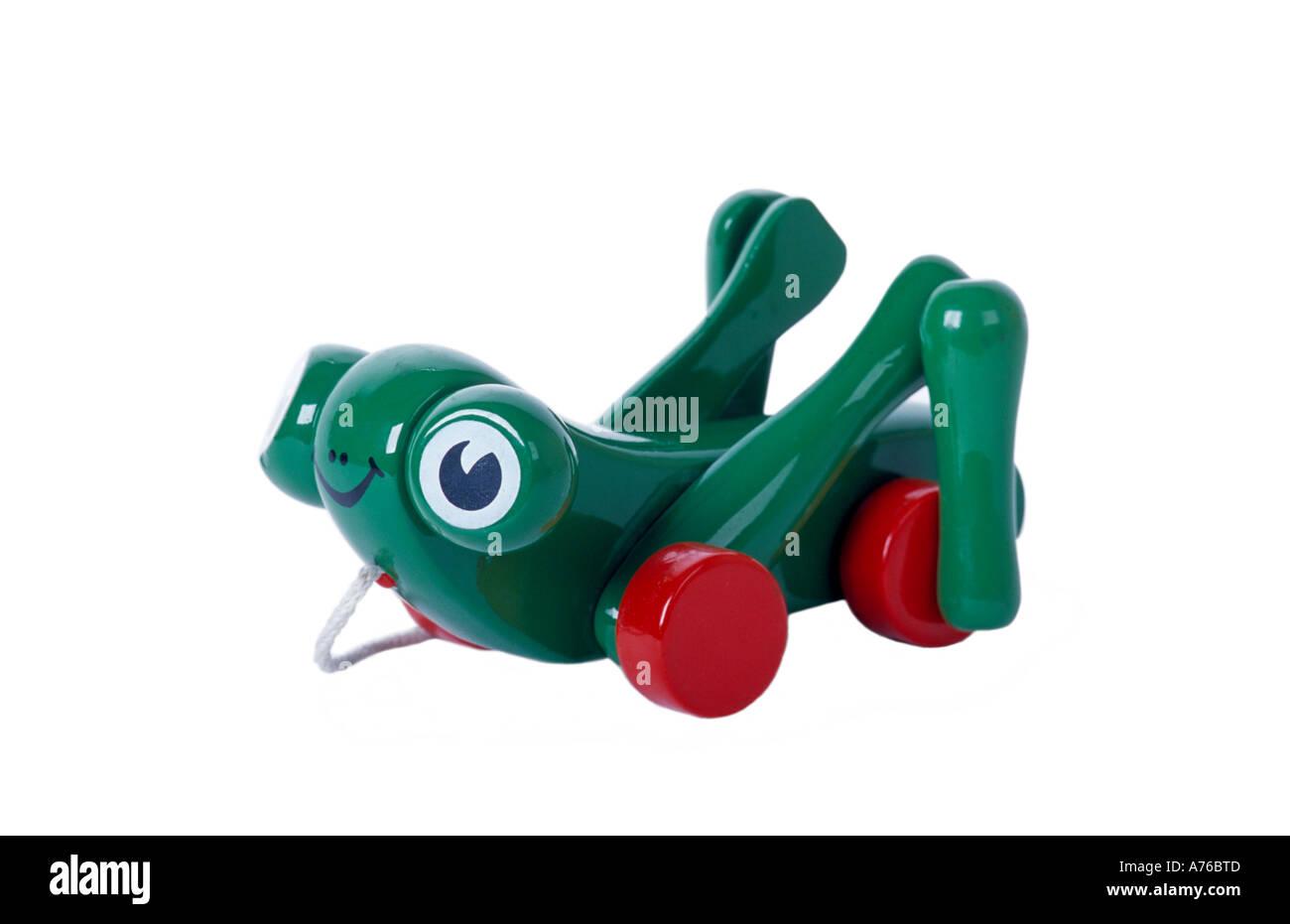 Tirez-le long de la grenouille jouet enfant sauterelle sur un fond blanc, pur. Photo Stock
