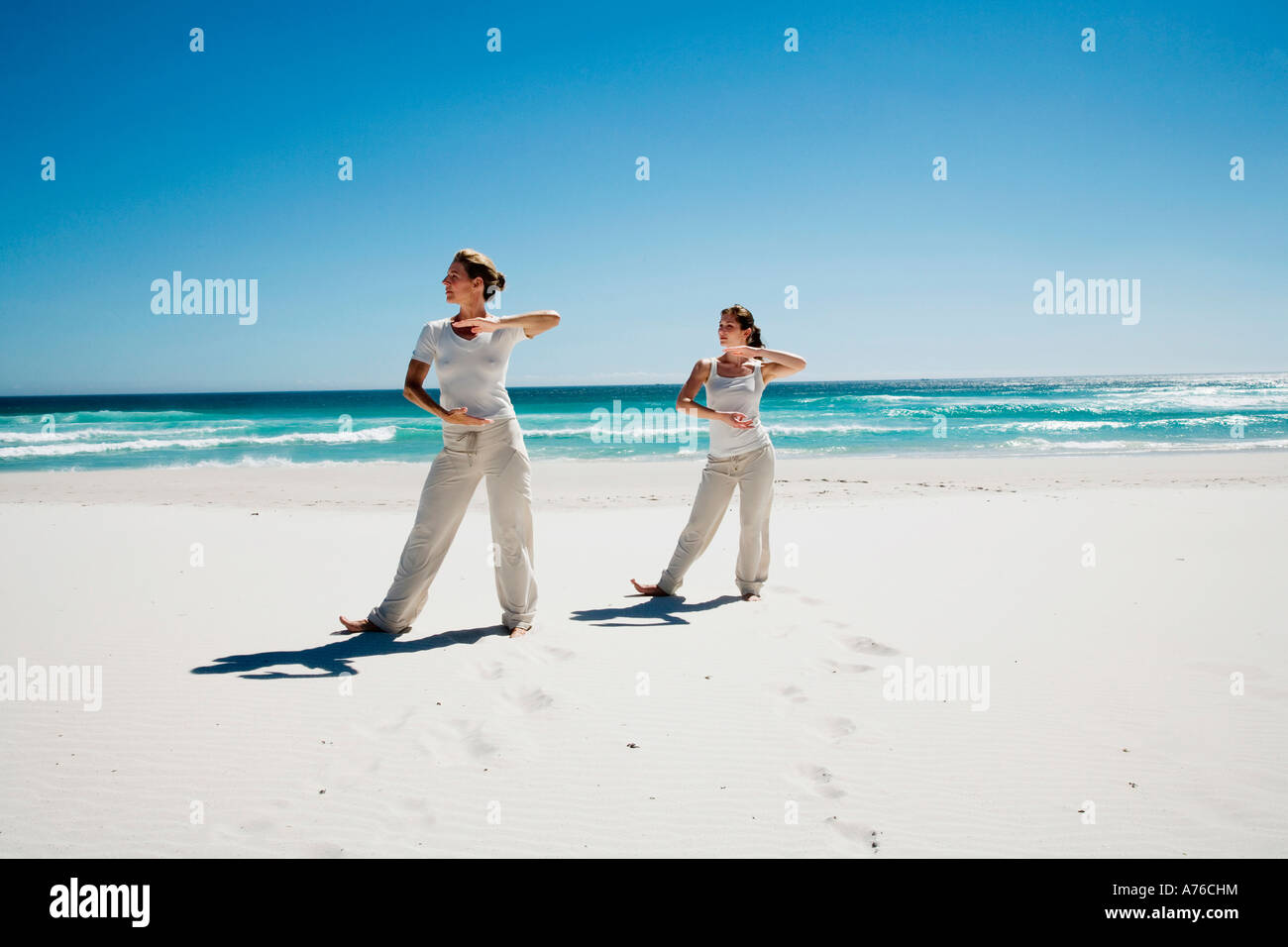 Deux femmes l'exercice de yoga on beach Photo Stock