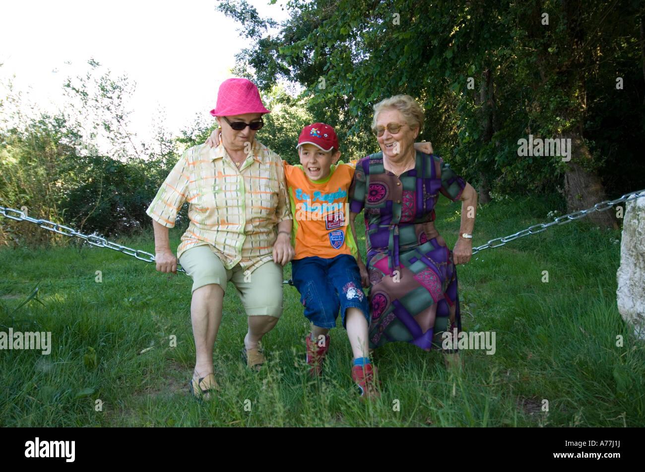 Deux vieilles dames et un jeune garçon se balançant sur une clôture enchaînés dans le pays Photo Stock