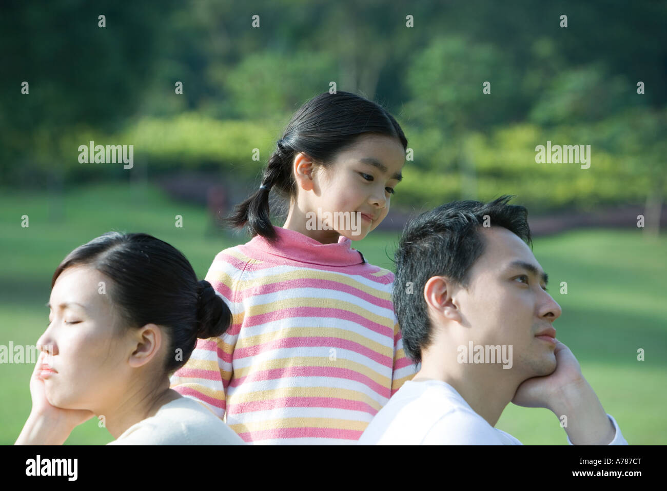 Girl parents assis dos à dos Banque D'Images