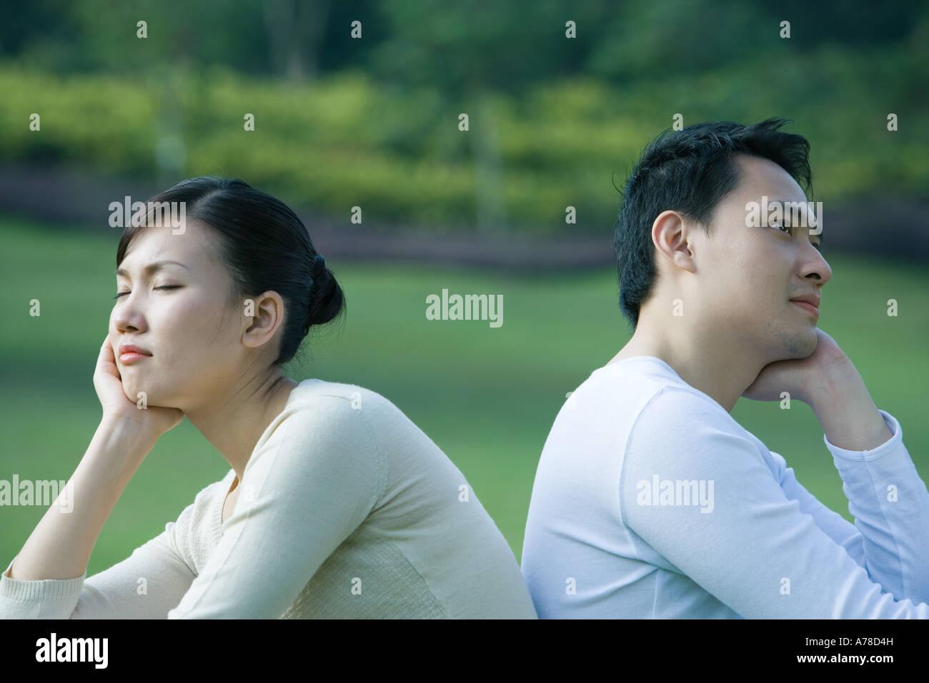 Couple assis dos à dos, tête dans les mains de repos Banque D'Images