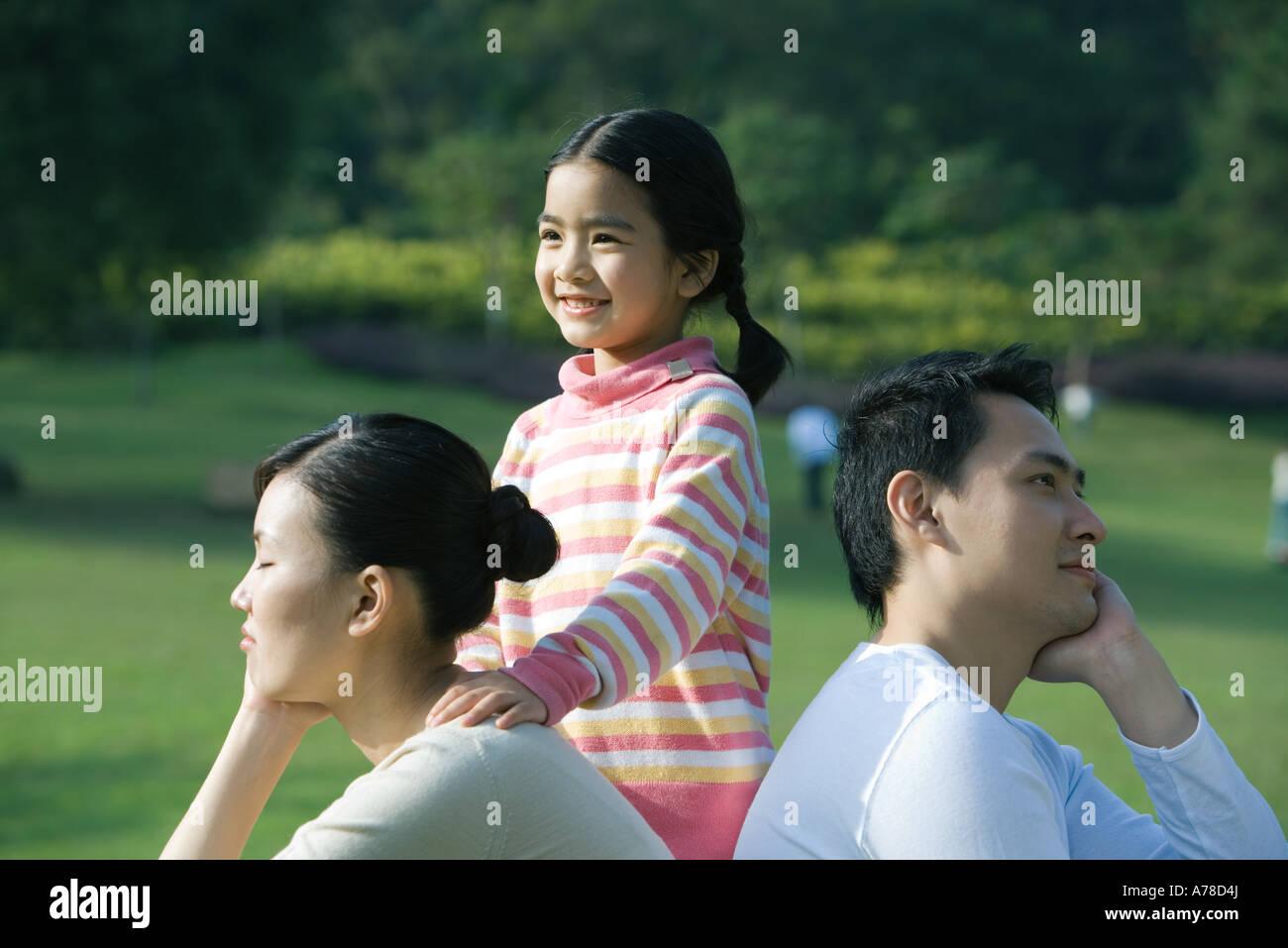 Couple assis dos à dos, fille debout derrière eux avec la main sur l'épaule de la mère Banque D'Images