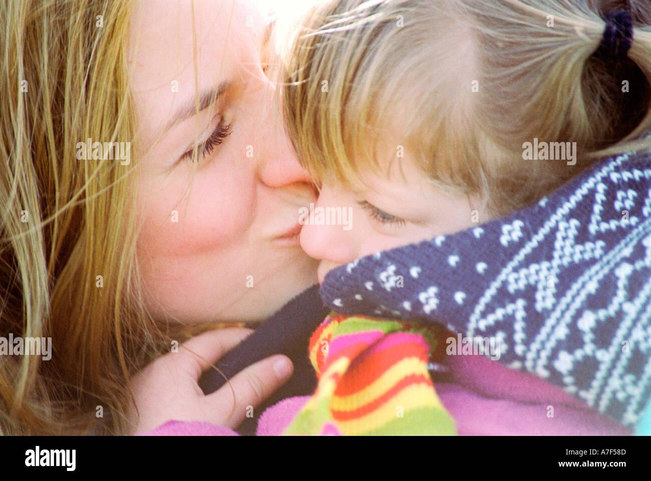 Mère embrassant sa fille alors que dans d'embrasser Photo Stock