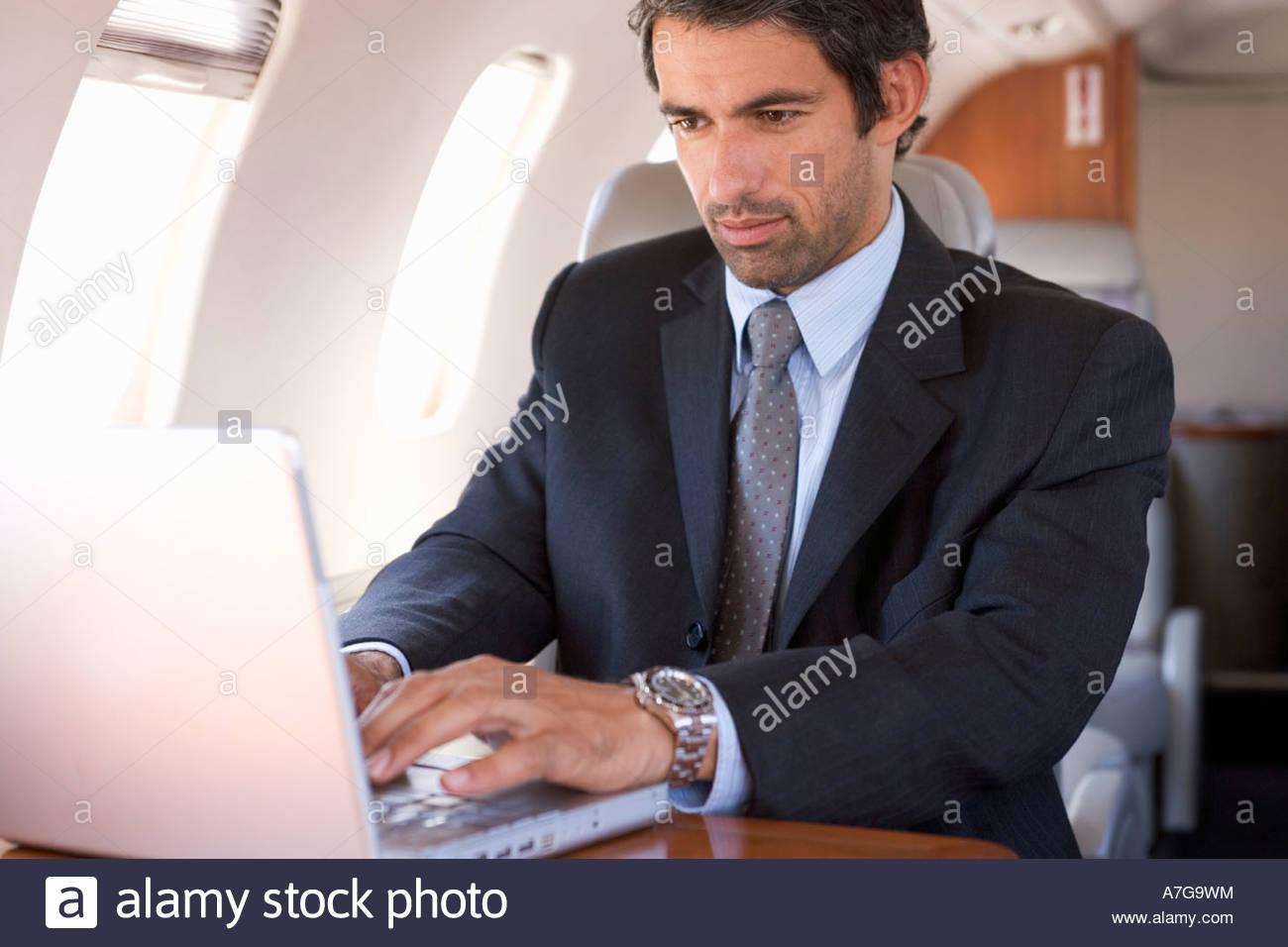 Un homme d'affaires à l'aide d'un ordinateur portable dans un avion Photo Stock