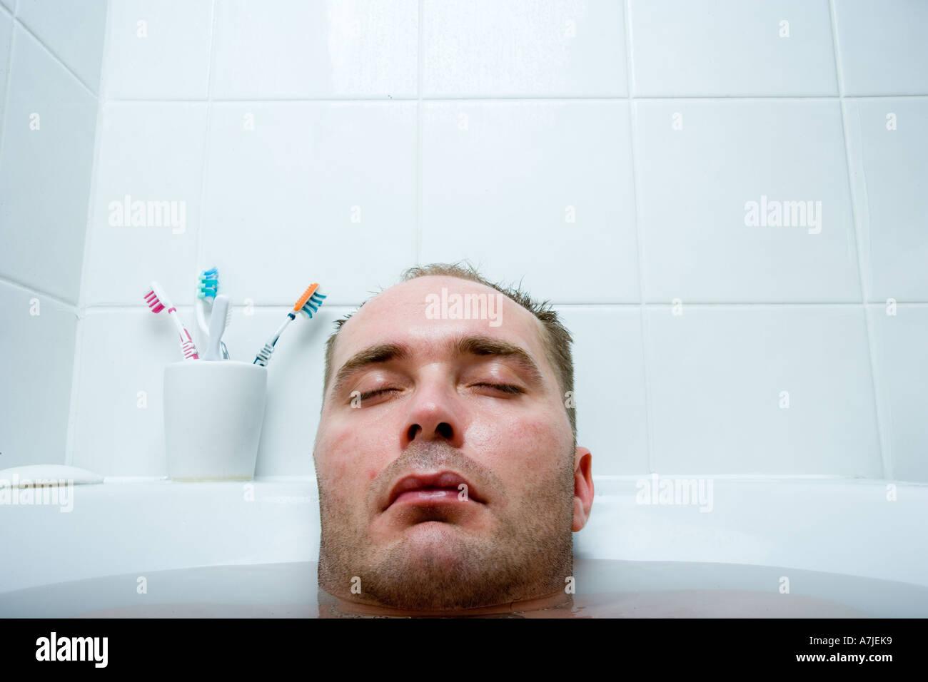 Tête d'un homme avec les yeux fermés et le reste de son corps plongé dans une baignoire Photo Stock