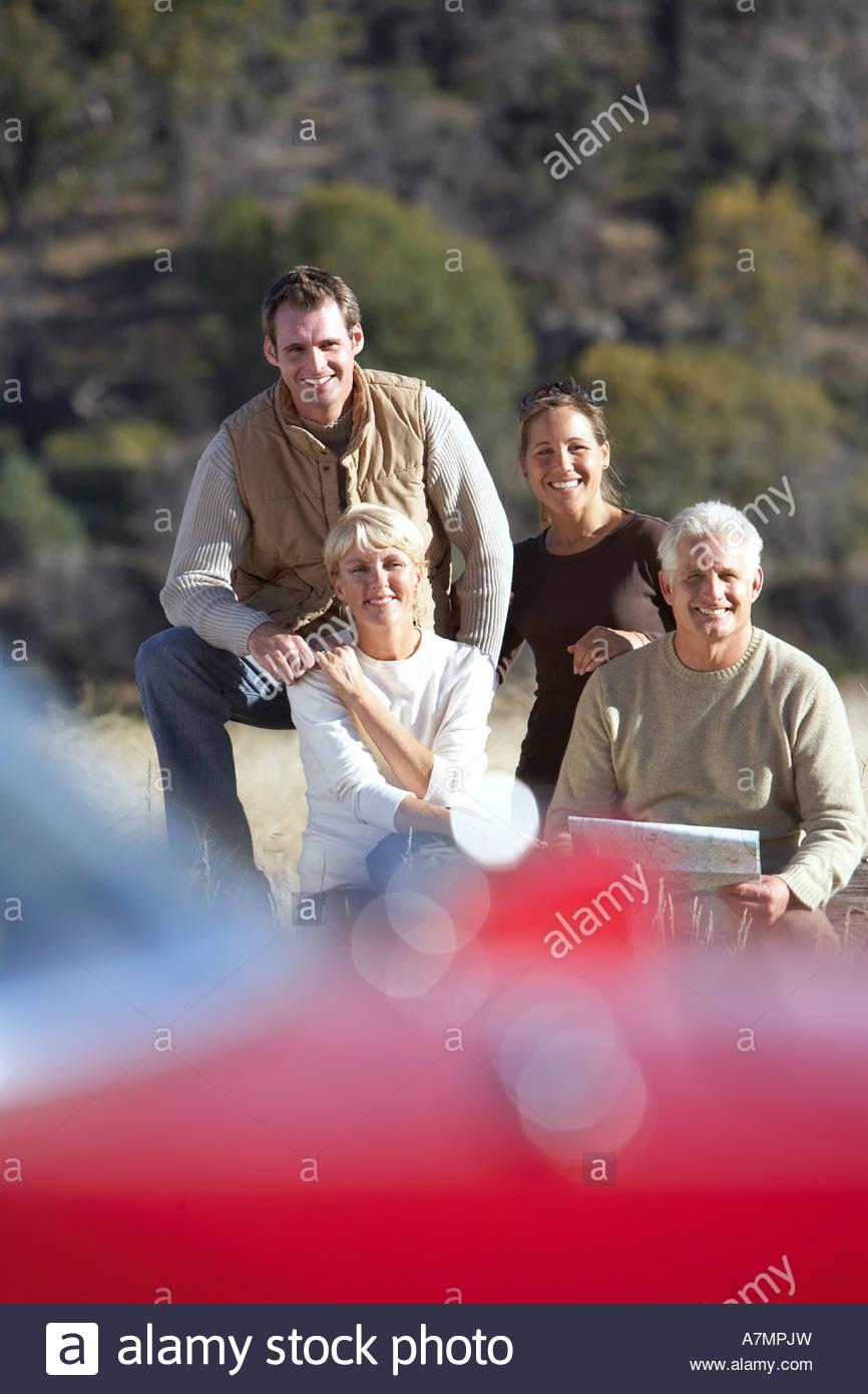 Deux couples à la recherche de route en pleine campagne smiling portrait accent sur l'arrière-plan Photo Stock