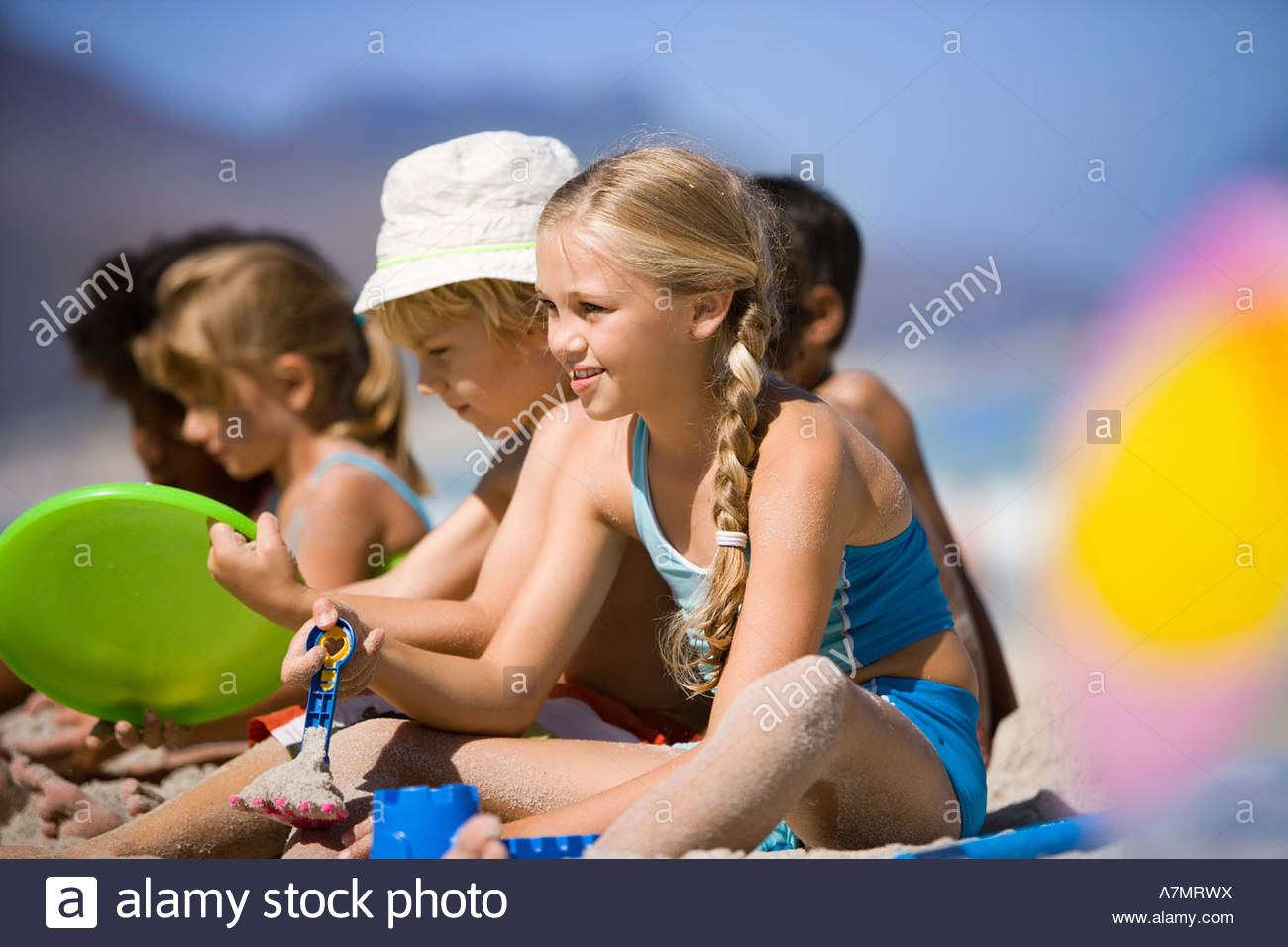 49 Enfants assis en ligne sur beach smiling side view differential focus Photo Stock