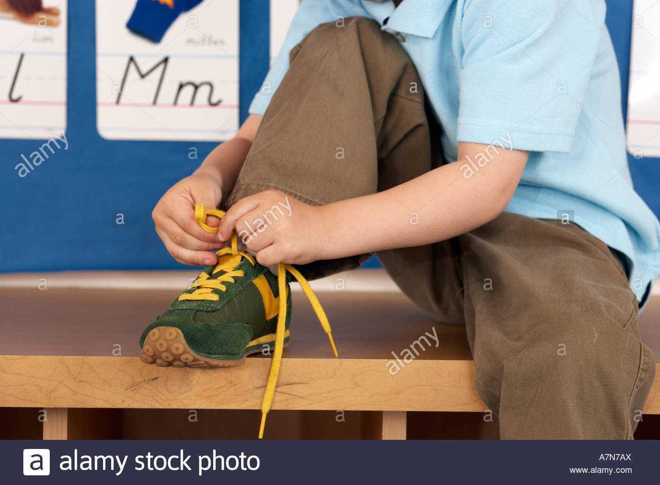 Boy 46 assis sur un banc en bas lacet jaune de liage en classe section cartes alphabet on wall Photo Stock