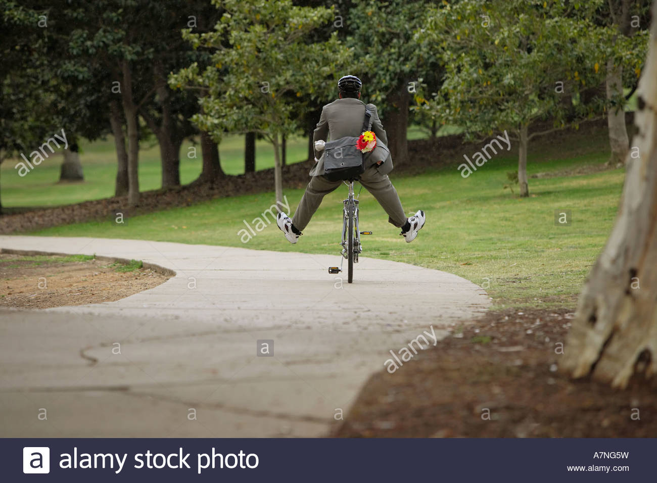 L'homme à vélo sur chemin dans les jambes du parc vue arrière Photo Stock