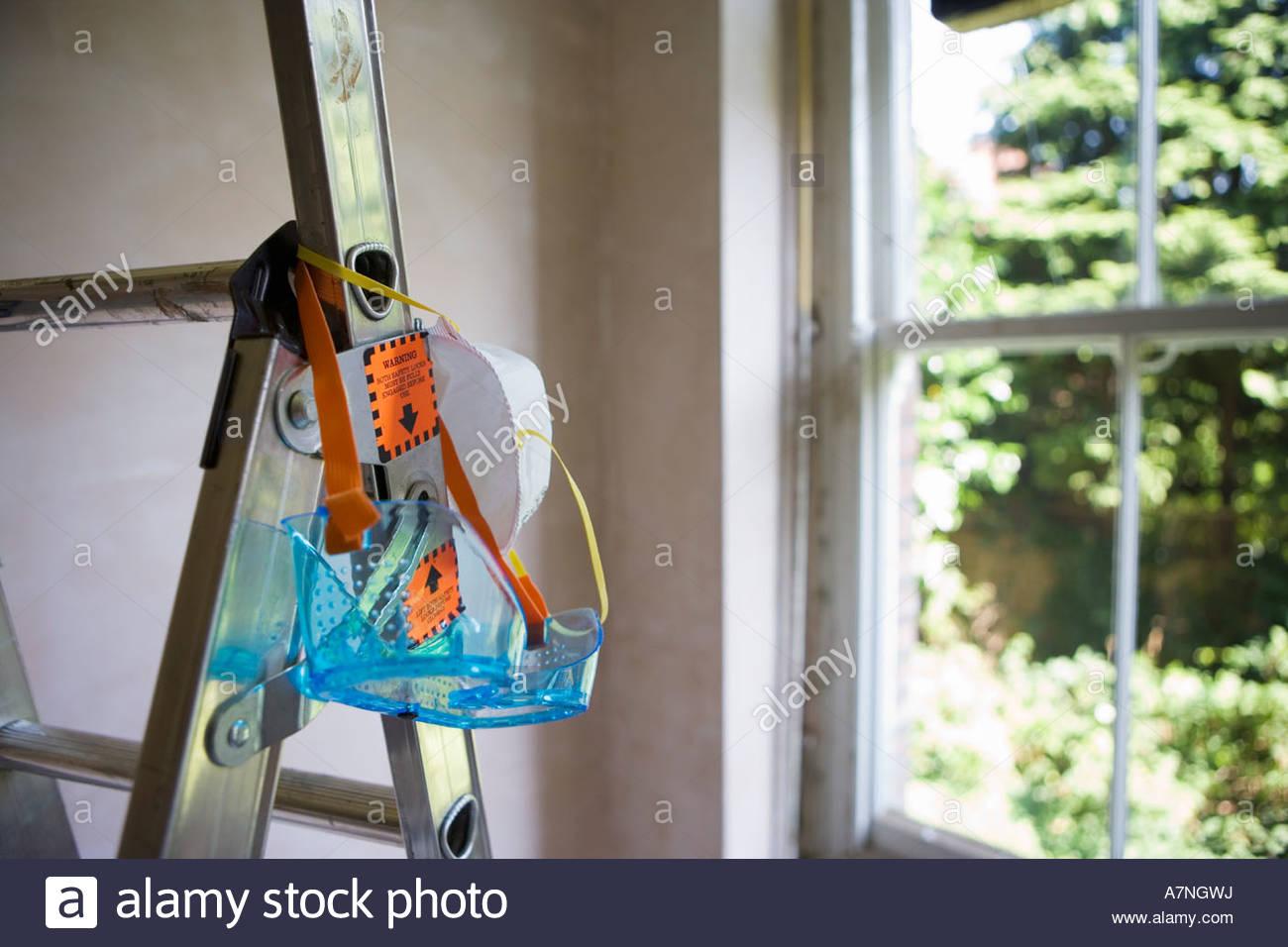 Des lunettes de protection et un masque anti-poussière accrochée à l'escabeau dans la fenêtre Photo Stock
