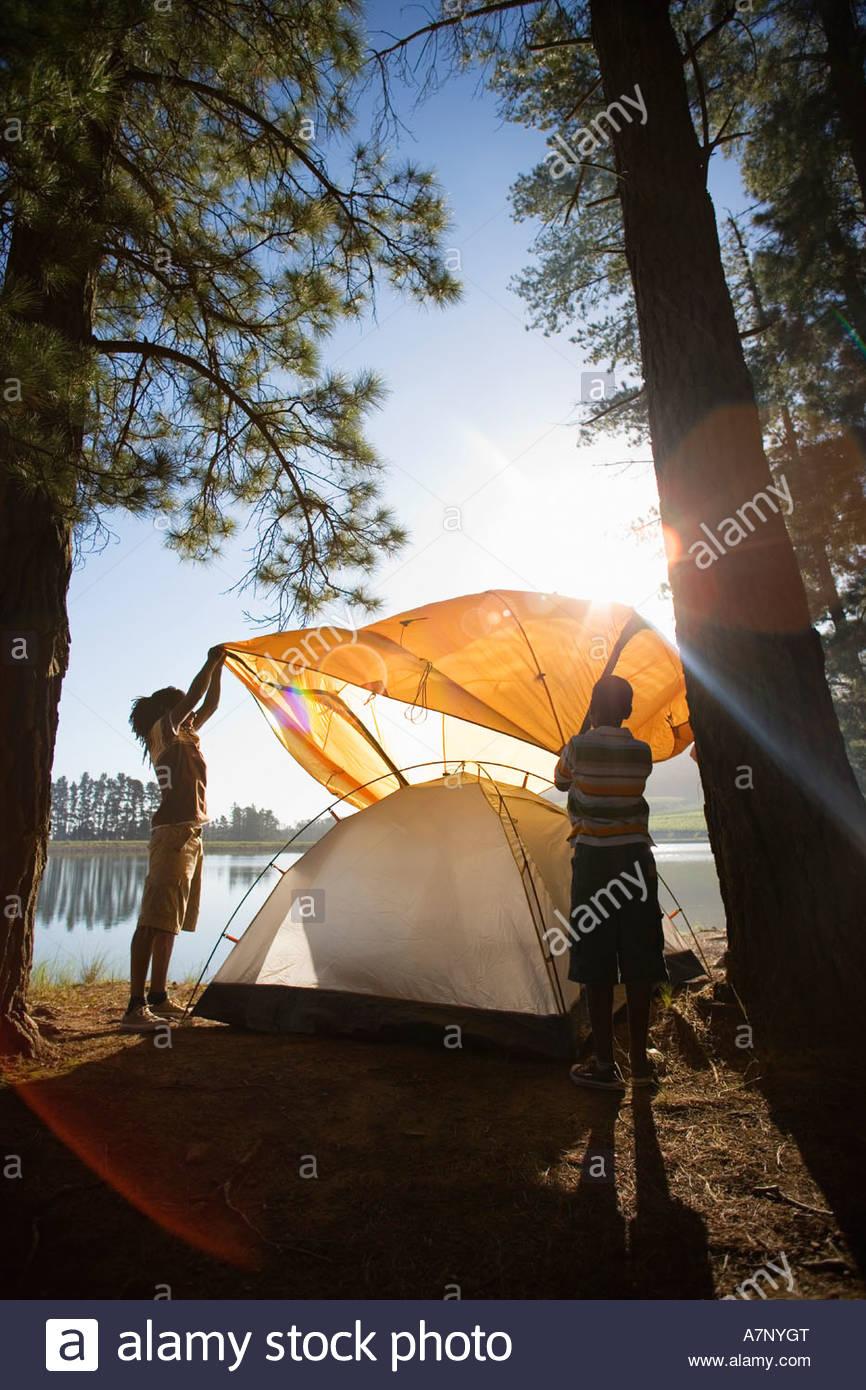 Père et fils 810 orange assemblage tente sur voyage de camping au bord du lac photo Photo Stock