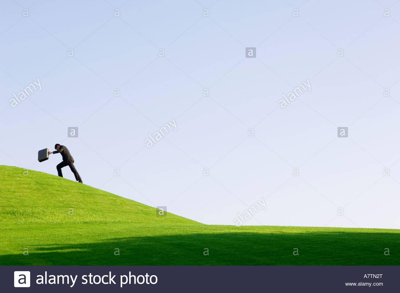 Un homme avec une valise la marche en montée Photo Stock