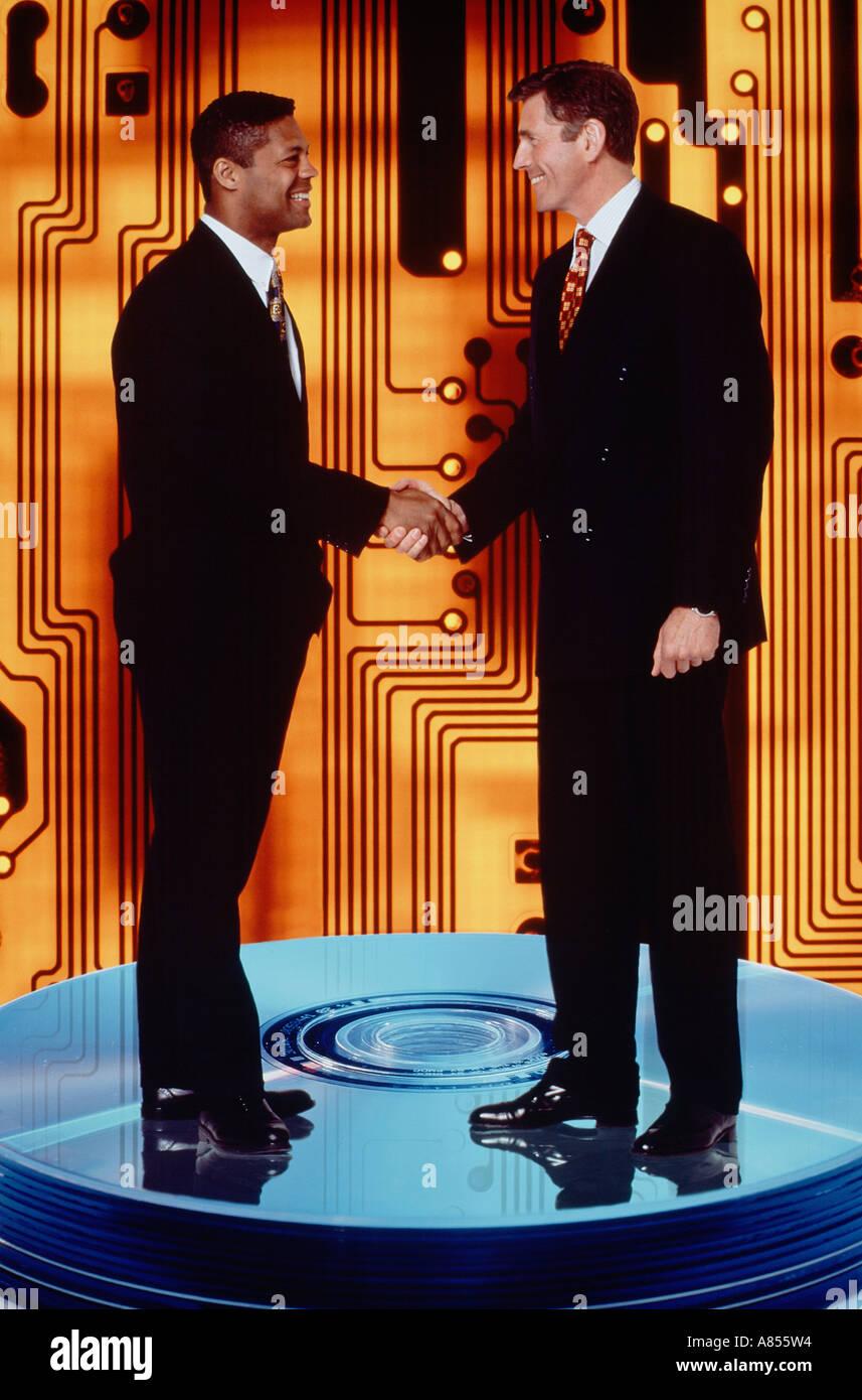 Concept. Deux hommes d'affaires handshake montaged sur disque informatique media et le circuit. Photo Stock