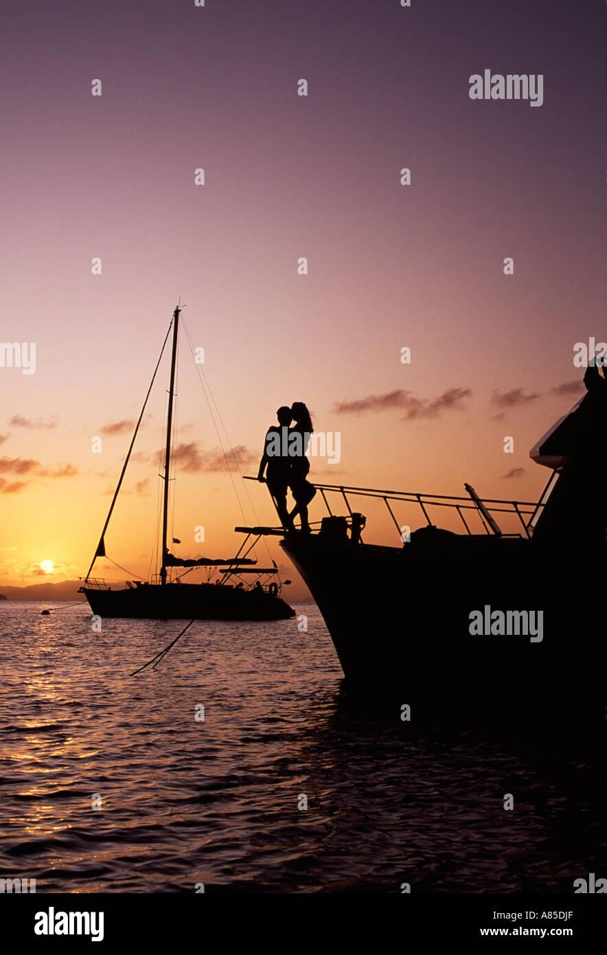 BVI Cooper Island romantic couple on bow de bateau ancré au coucher du soleil Banque D'Images
