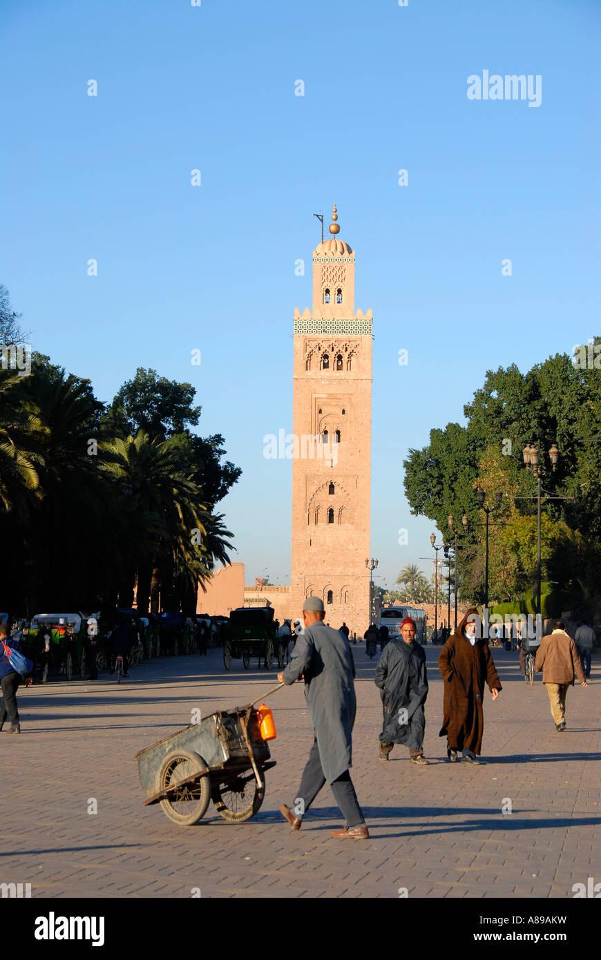 L'homme pousse un barrow sur la place de Foucauld Djemaa el Fna avec un minaret de la mosquée de Koutoubia dans le dos Marrakech Maroc Banque D'Images