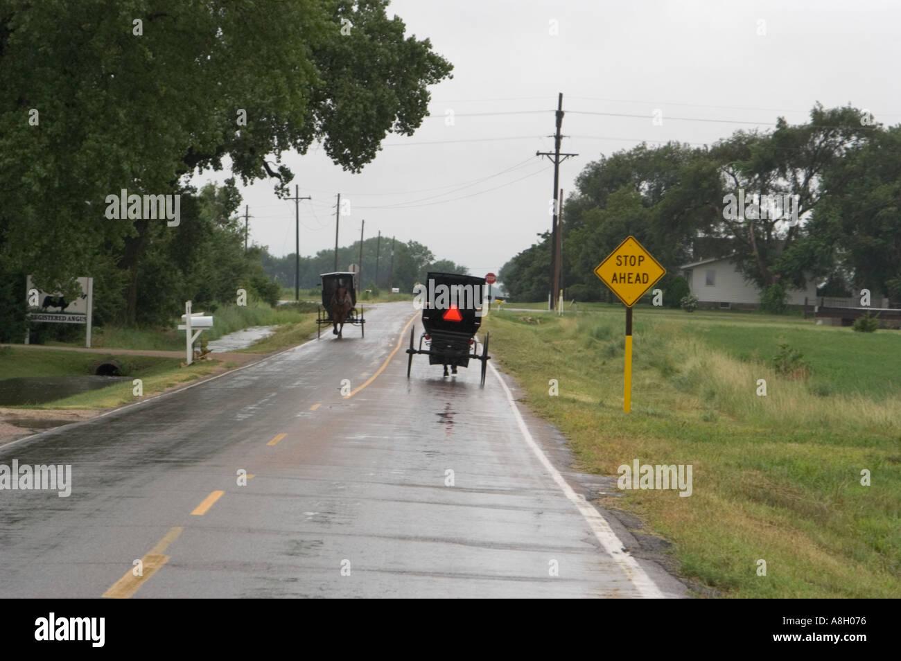Voitures Amish sur route lissés pluie Yoder Kansas Banque D'Images