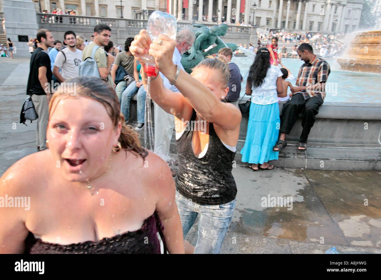Deux jeunes femmes jouent avec l'eau des fontaines à Trafalgar Square, Londres Photo Stock