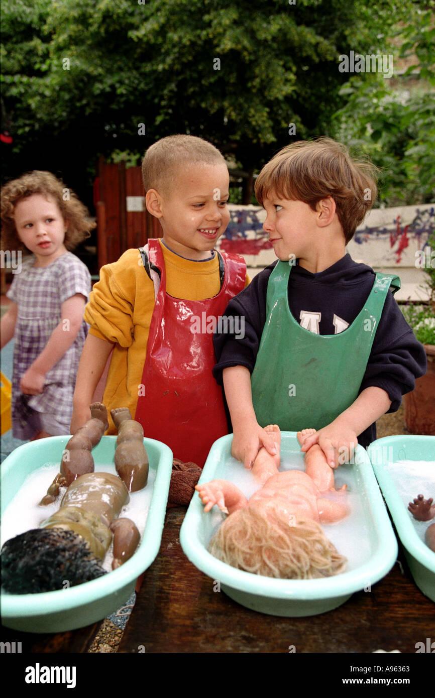 Deux garçons poupées de baignade en plein air à la pépinière. Banque D'Images