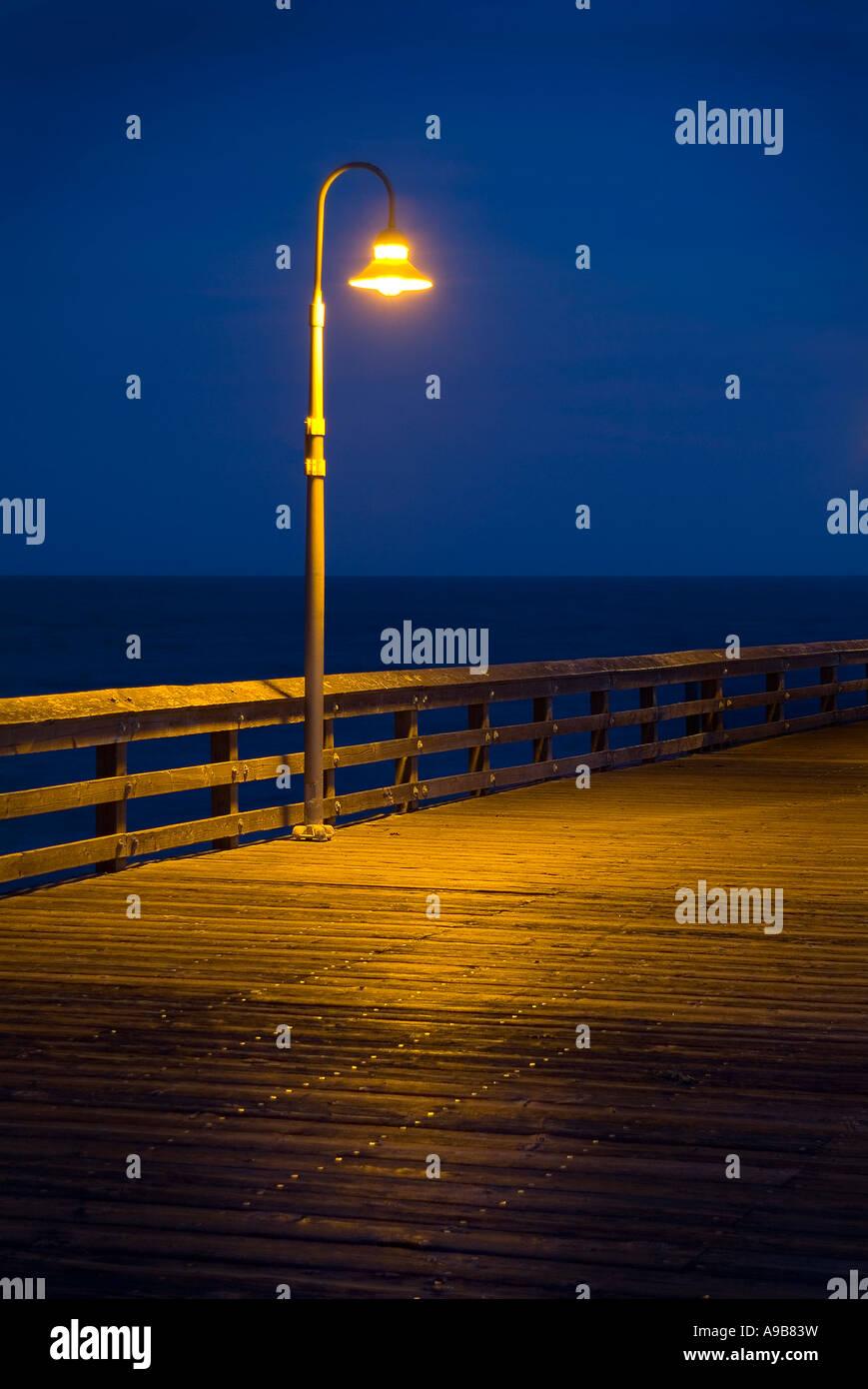 lampadaire solitaire bord de marche avec la lumi re allum la nuit pr s de l 39 oc an jet e de. Black Bedroom Furniture Sets. Home Design Ideas