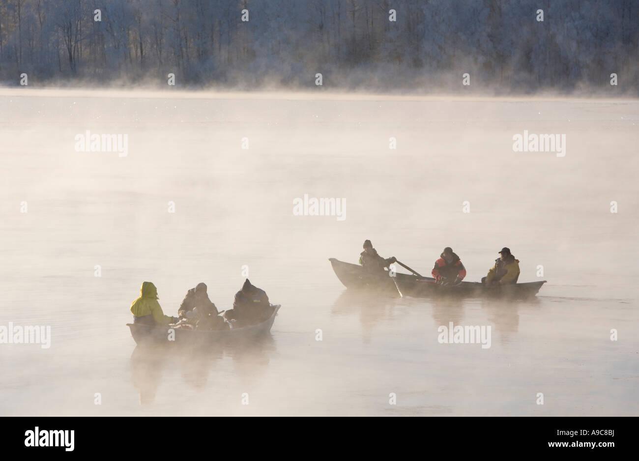 Turlutte lavaret pêcheurs de chaloupes à Rivière froide journée d'hiver de Oulujoki , Finlande Photo Stock