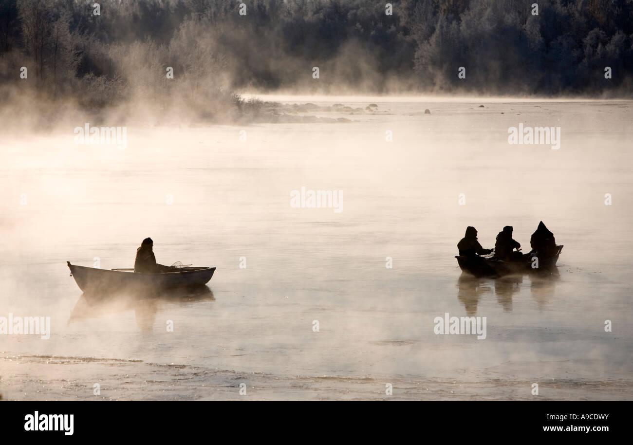 Turlutte pêcheurs des ciscos de chaloupes à froide journée d'hiver à fleuve Oulujoki , Finlande Photo Stock