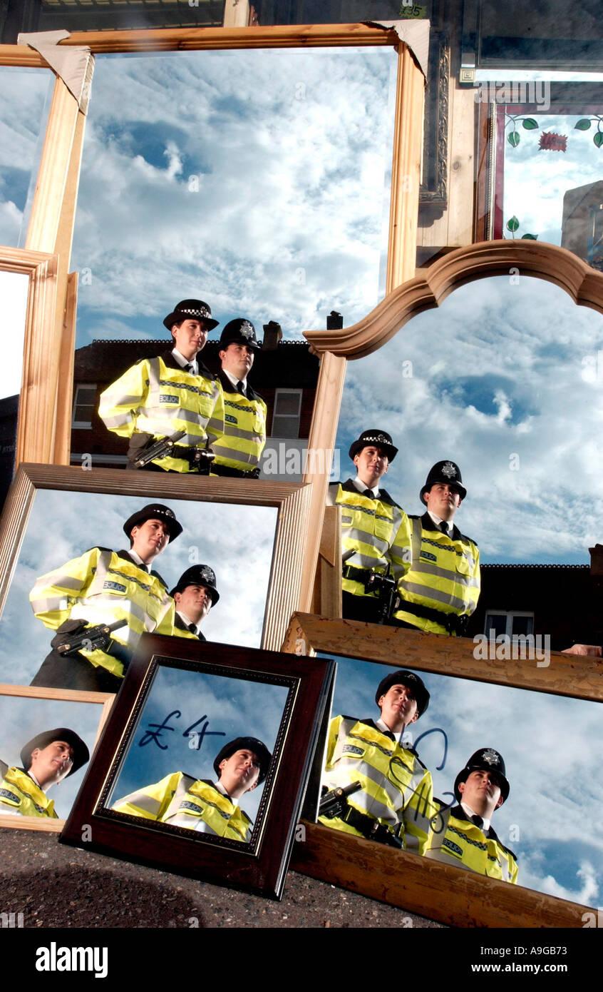 Deux policiers en uniforme. un mâle une femelle, d'une patrouille à pied reflète encore et encore dans les miroirs dans une vitrine Photo Stock