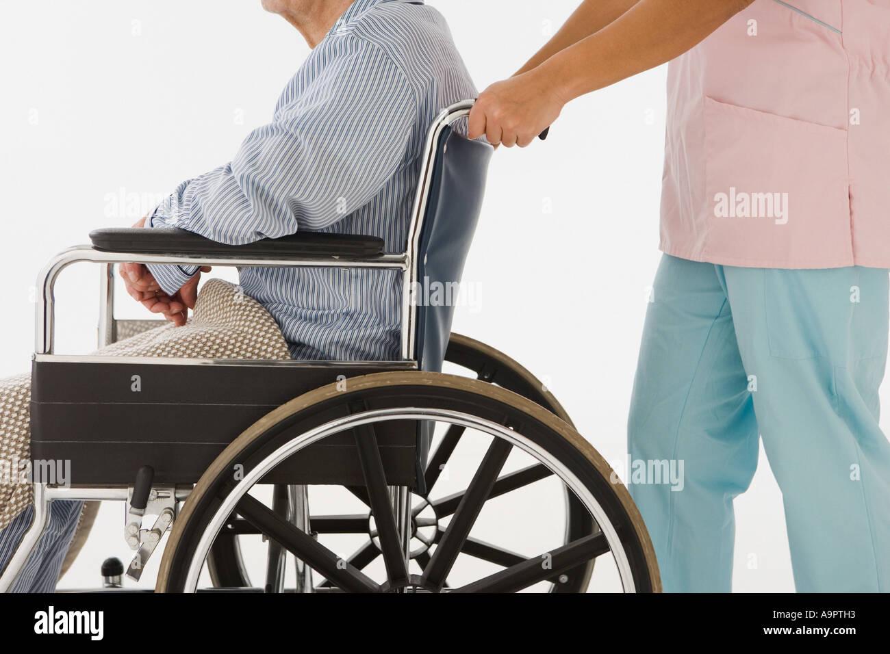 Nurse pushing man in wheelchair Photo Stock
