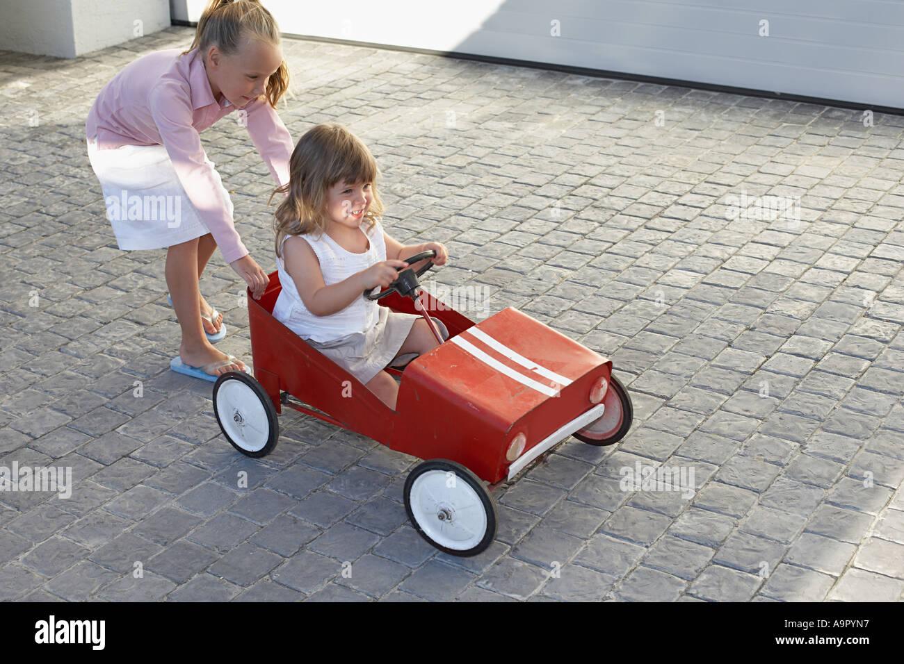 Sœur de pousser sa sœur dans une petite voiture Photo Stock